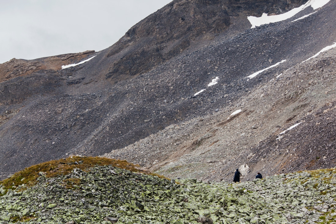 2 figures in the landscape of layered rock at the Col de Plan Séry in Vanoise National Park.