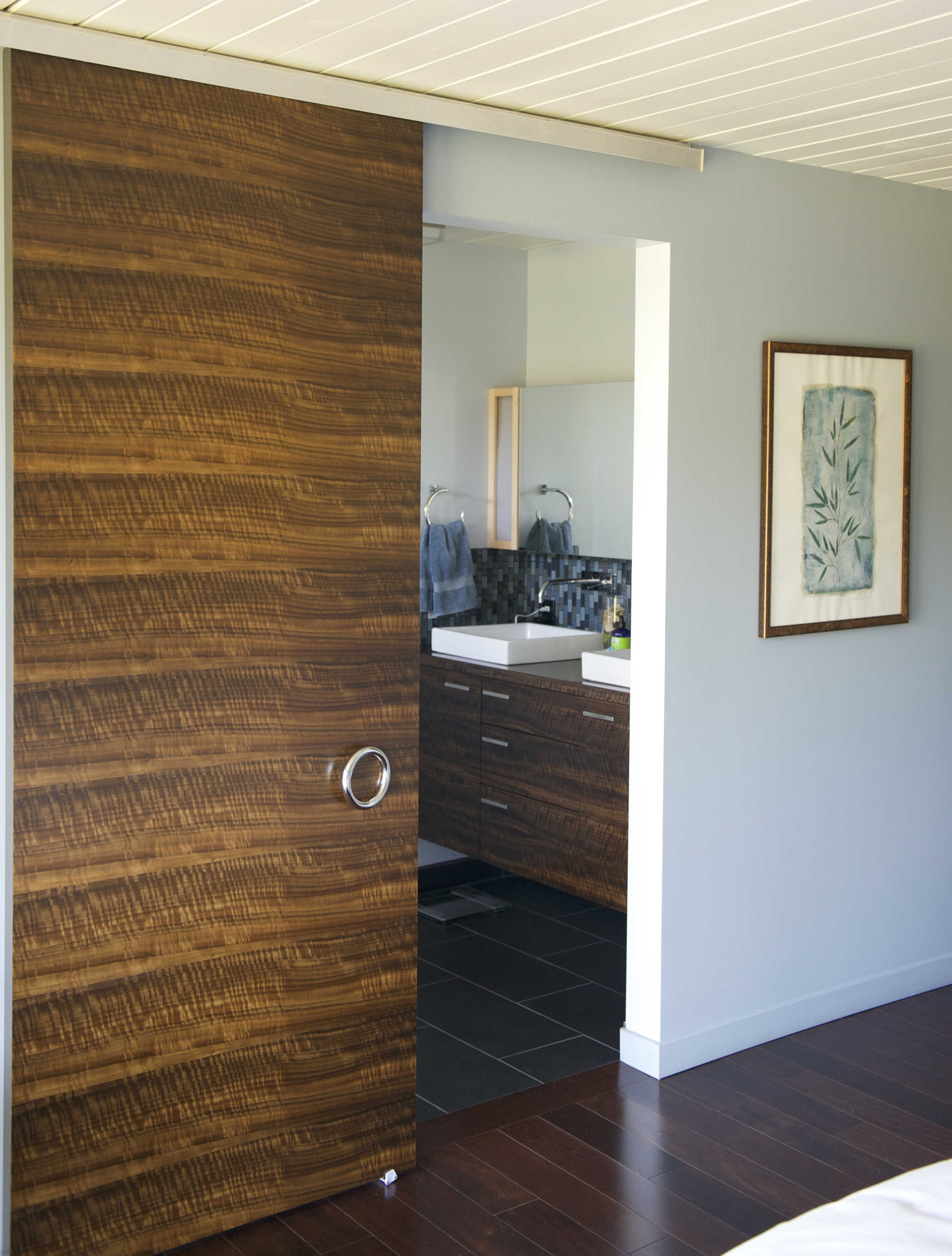 The master suite door, master bath door, and vanity are of fumed Eucalyptus. This is a process where the veneers are exposed to ammonia until they acquire the desired darkness. Too long exposure will turn them black. There is no dye or stain used in this process.