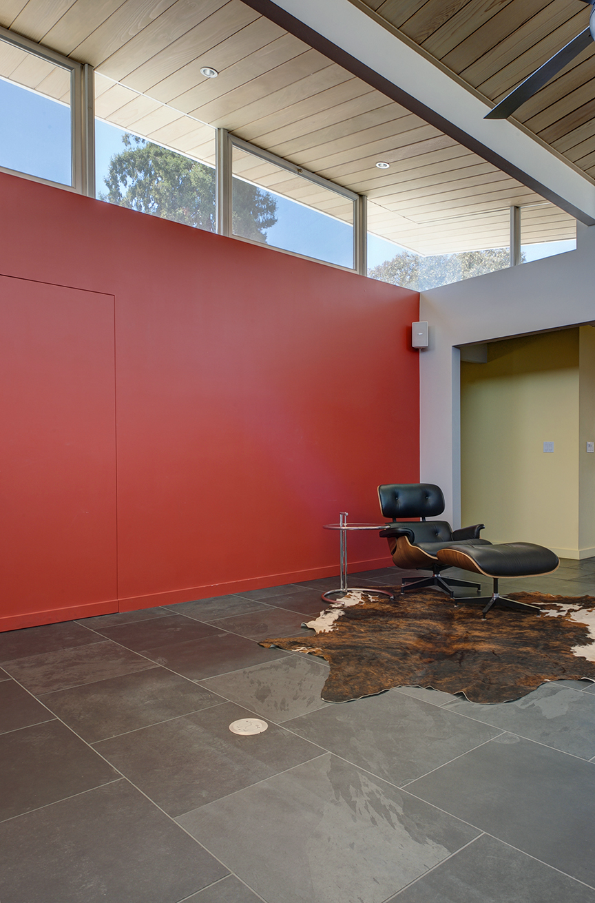 The bold red wall accentuates the atrium's floating roof. The use of strong primary colors is balanced out by neutral grays, and the natural wood ceiling.