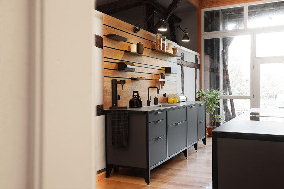 Das praktische Wandpaneel Regal-System hat alle Utensilien zum Kochen griffbereit an der Wand.