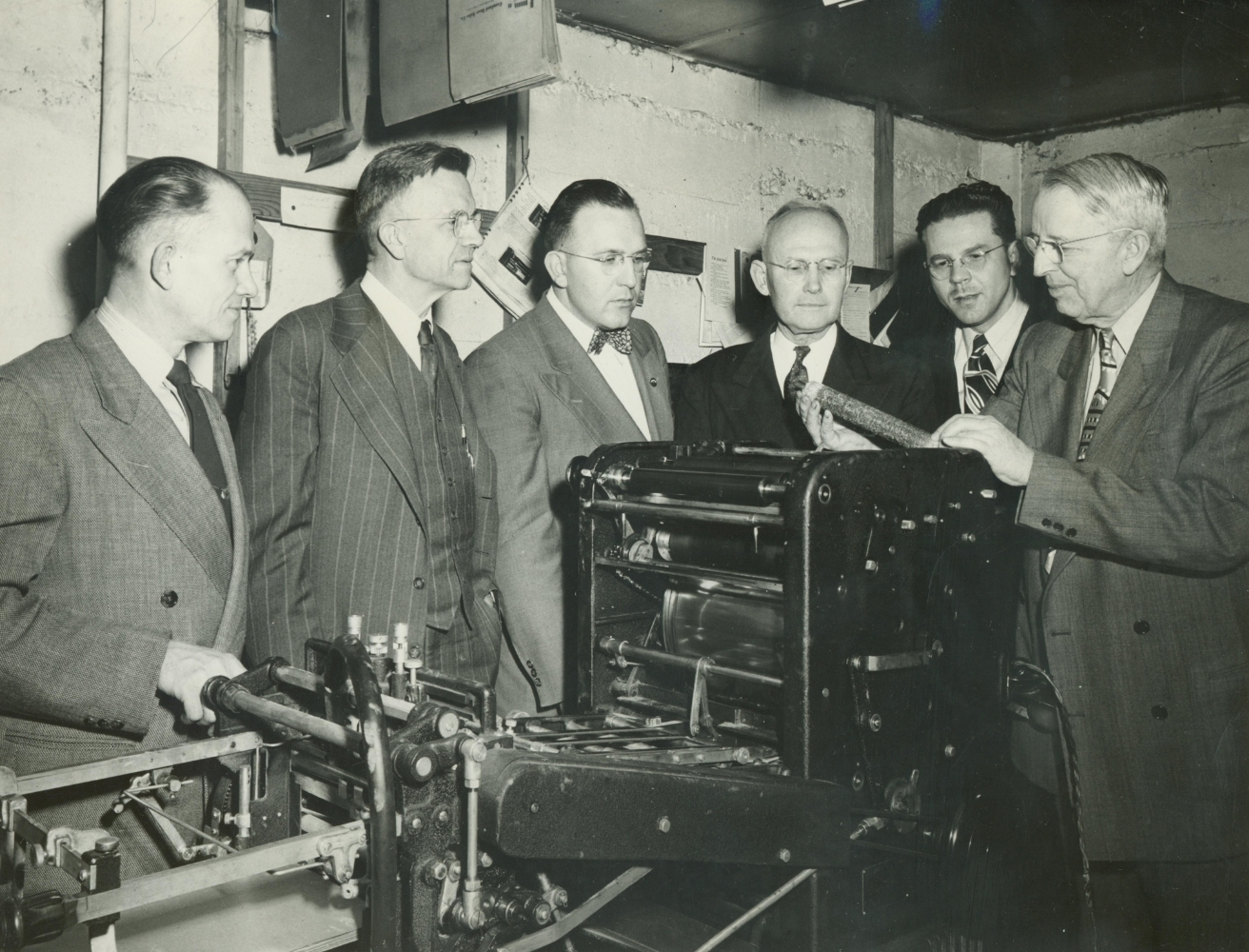 Ray Carter (right) shows a newly acquired press to the Oregon Yearly Meeting publications board.