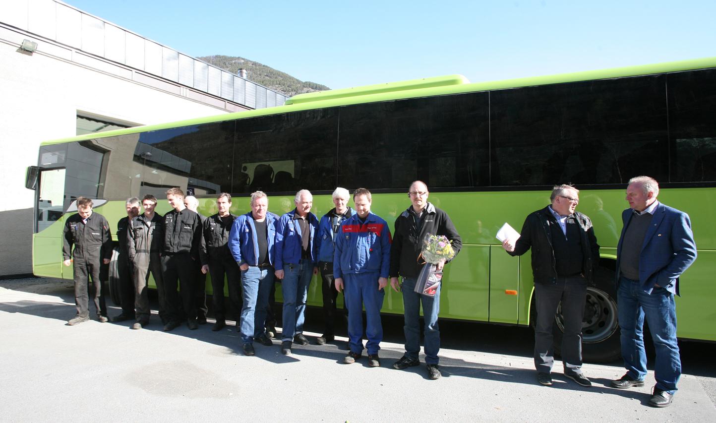 Dei tilsette med den første bussen som er blitt lakkert i den nye lakkhallen.