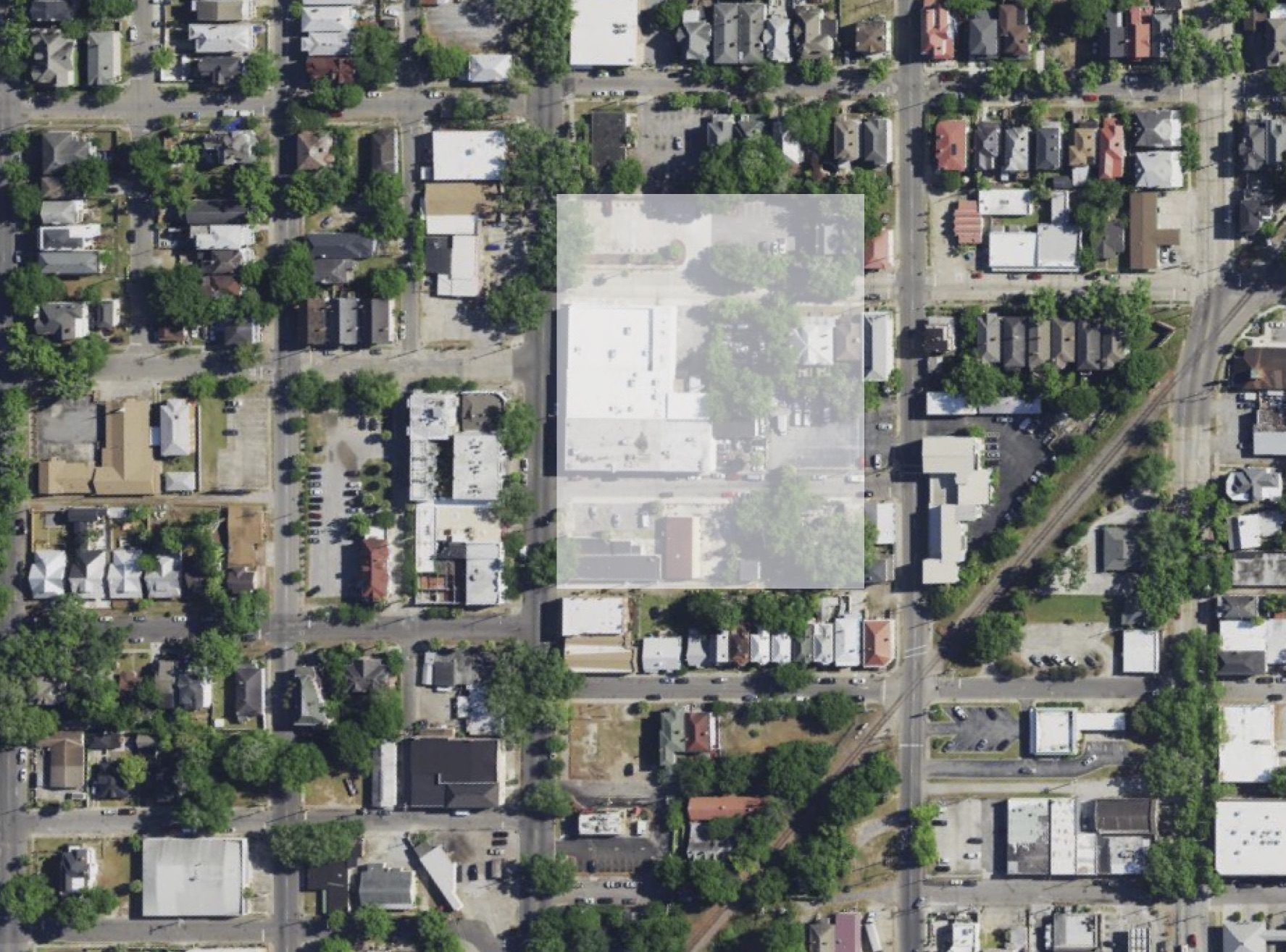 """Before"" image of one location of a potential garage. A one-story, former grocery and its parking is the site in the middle."