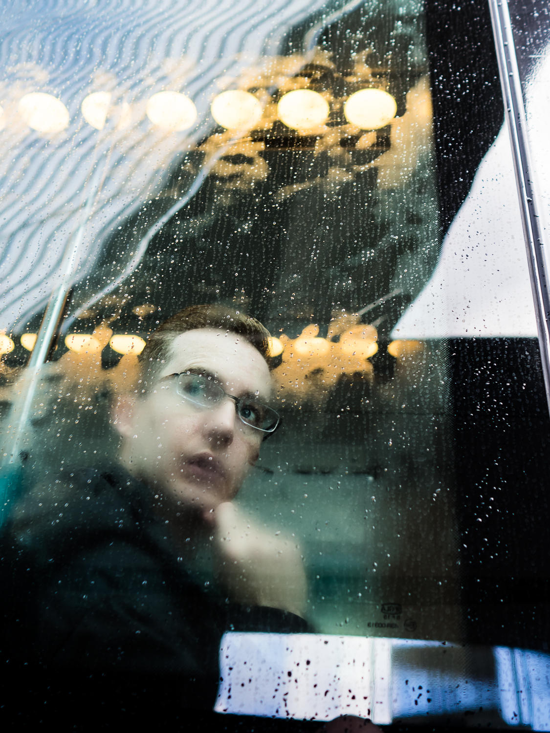 RotTERDAM november 2016  Shot taken at the Central Station.  I always join the participants of my street photography workshops to shoot through glass barriers. In this case I was happy to see this guy behind a steamy window of the tram. Part of my    Glassy    series.  Shot with Olympus OMD5 Mark 2 and Olympus 17mm f/1.8