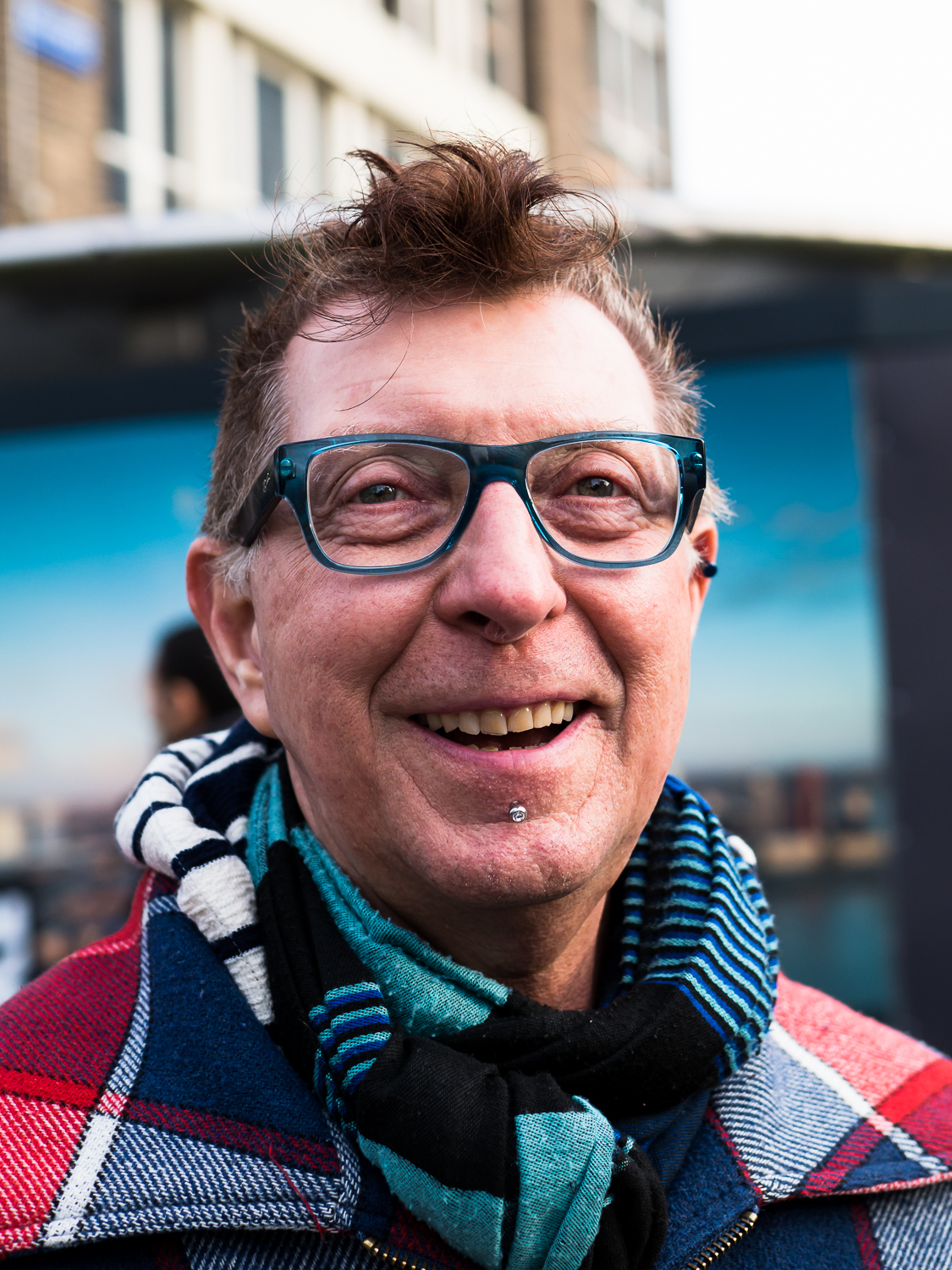 Photo taken in Rotterdam in March 2017. Sometimes I make street portraits with permission of the model. This guy lives in Emmen but was born in Rotterdam. It was a long time since he visited Rotterdam and he told me that he got quite emotional touching the Rotterdam ground again. His name is Eddy Tijssen. His colorful clothes and his friendly open face caught my intention.  Shot with Olympus OMD1 Mark 2 and Olympus 25mm f/1.2. The 25mm is perfect for this kind of portraits. Look how sharp it is!