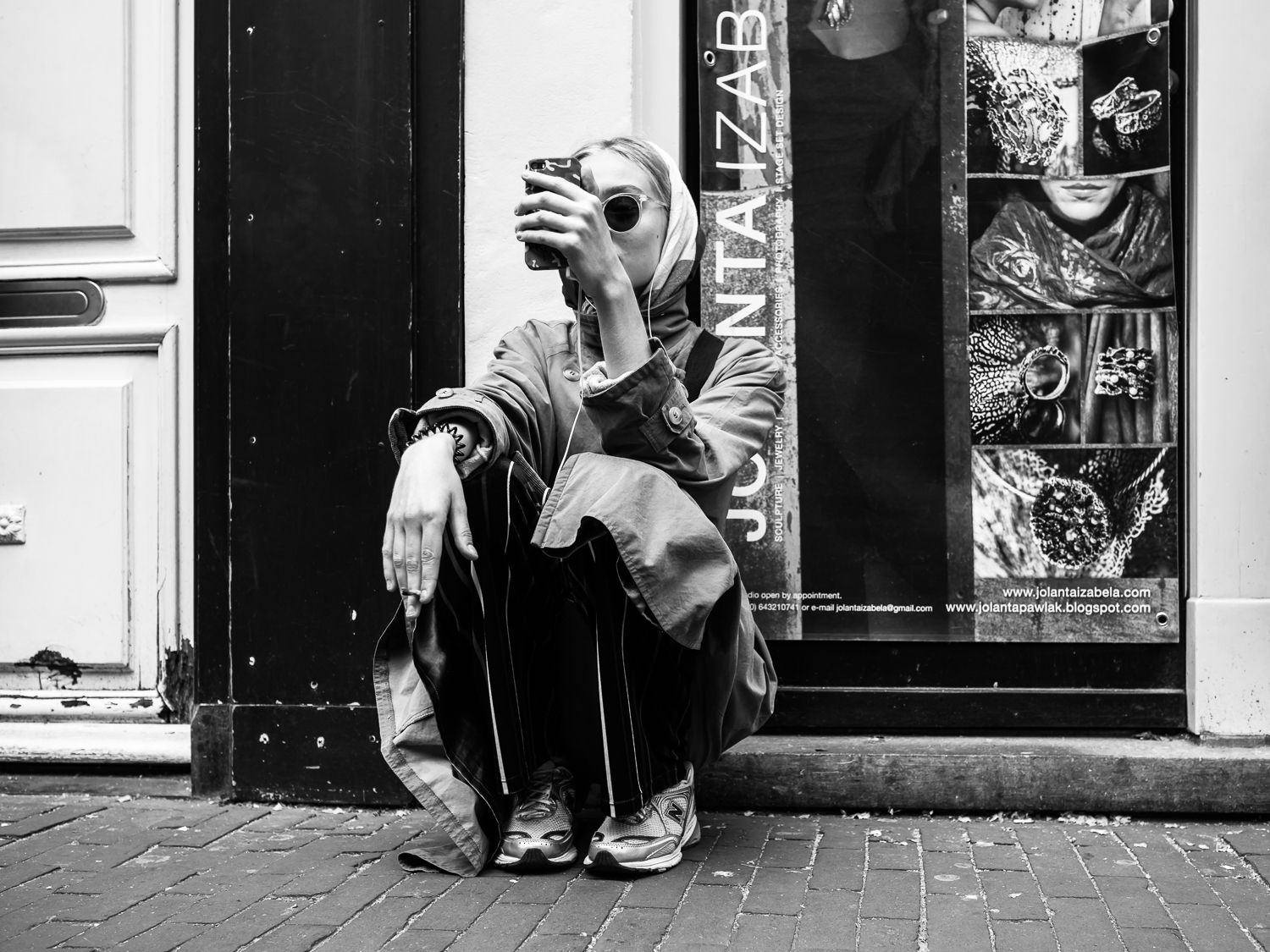 I made this photo during my workshop street photography in Amsterdam in May 2018. I immediately saw that she would fit in my   Undercover   series. I had to act fast as I wanted her face not recognisable. What I like is the way she is sitting, smoking a joint and talking to her phone. This is one of the first photos I made with my new Olympus 17mm 1:1.2 PRO lense. What a fantastic lens! Happy to be Olympus Visionary ;-)  Olympus OM-D E-M1 Mark 2 with Olympus M.ZUIKO 17mm 1:1.2 PRO