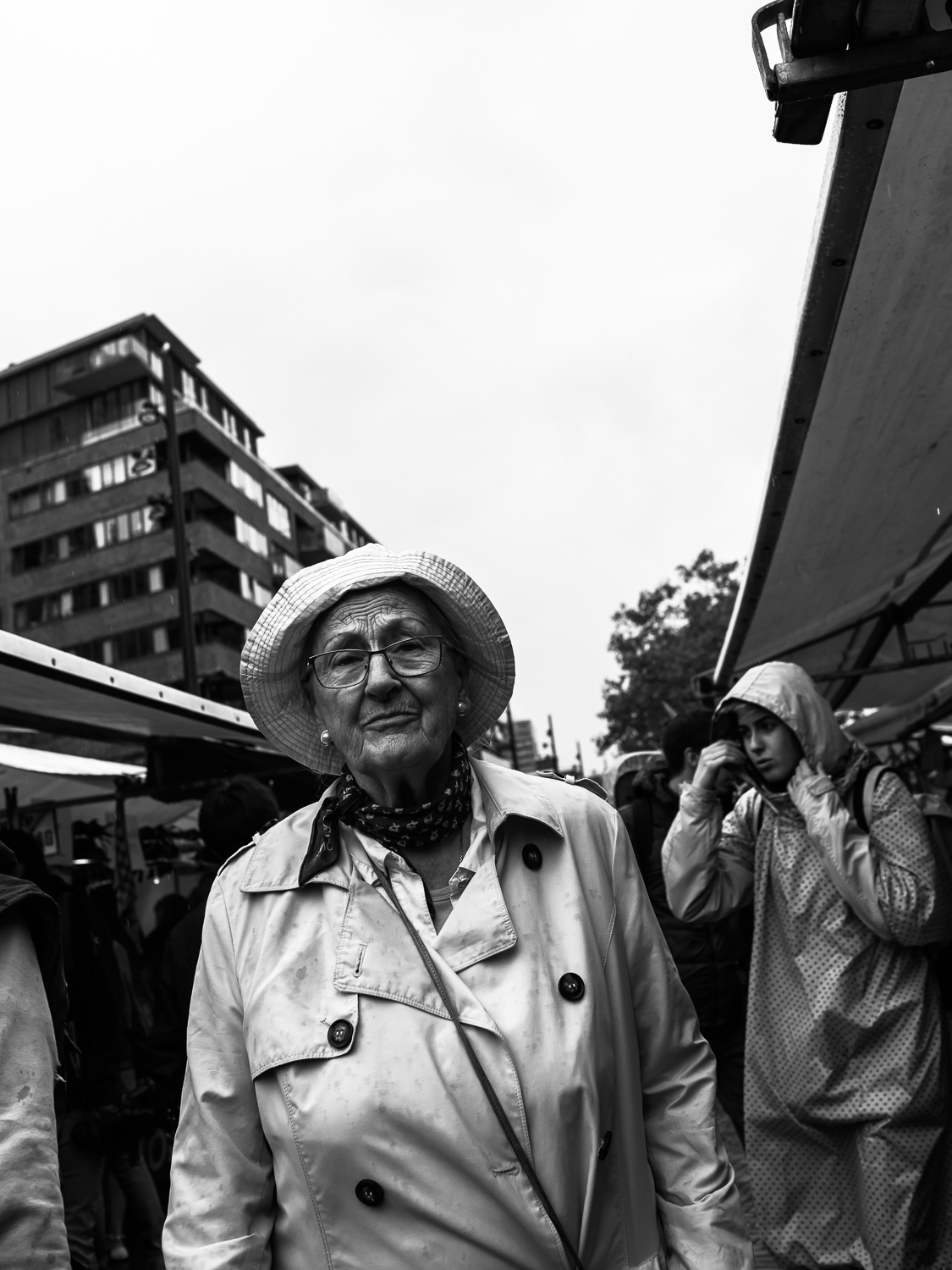 Rain gives interesting opportunities, for instance how people dress. On the Rotterdam Binnenrotte market I noticed this woman in old-fashioned rainwear. A more new-fashioned version can be seen in the background. I followed this lady for a while, walked past here, turned around and made the photo.  Olympus OM-D E-M1 Mark 2 with Olympus M.ZUIKO 17mm 1:1.2 PRO