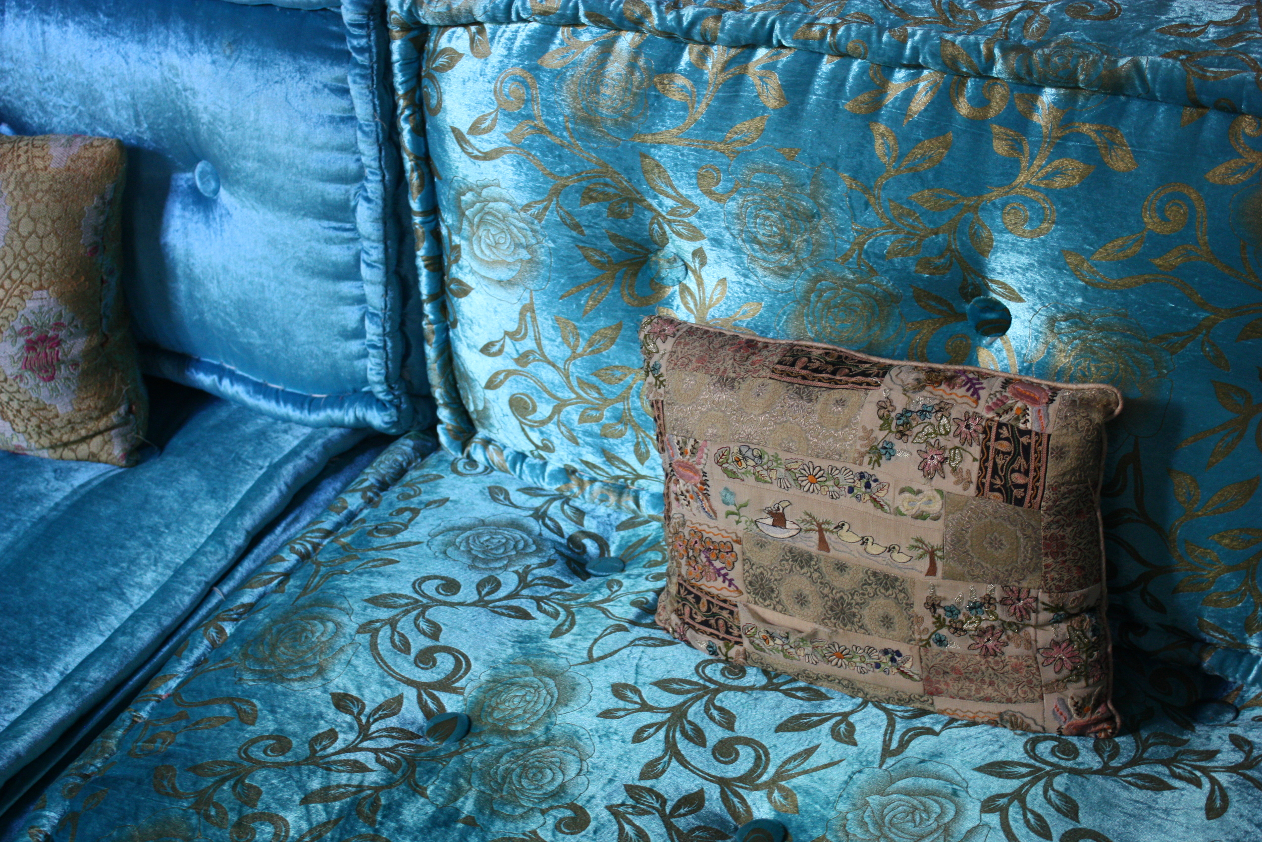 Old-fashioned plush velvets in luscious jewel colors are traditional in the Moroccan version of the divan, here combined with a delightfully embroidered pillow. From a riad salon in the old city of Fez in Morocco.