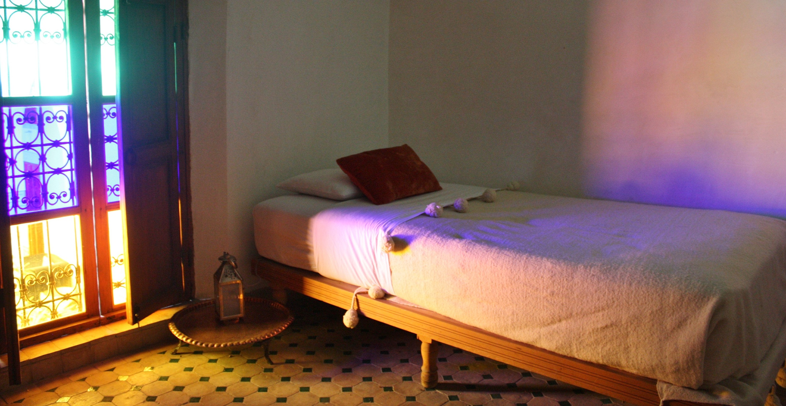 A simple bedroom in a riad in the old city of Fez displays the stunning colors, textures, and handmade textiles found in traditional Moroccan interiors.