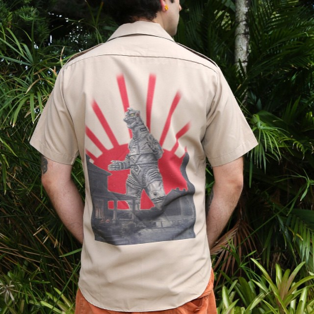 """#Handcrafted #Vintage #Military Tan #Mechagodilla short sleeve shirt. Ultra soft sublimated """"Mechagodzilla"""" #FineArtPrint by renowned #artist """"#MICHAELMARARIAN"""" on back. This unique #1960's khaki button down shirt is in incredible condition for a vintage piece and features the #Japanese characters for Mechagodzilla on the front left #pocket. This one of a kind dress shirt with """"Mechagodizlla"""" print will keep the heads turning ... Great for eating #sushi, trips to #MonsterIsland, saving #Tokyo, and your self-esteem."""