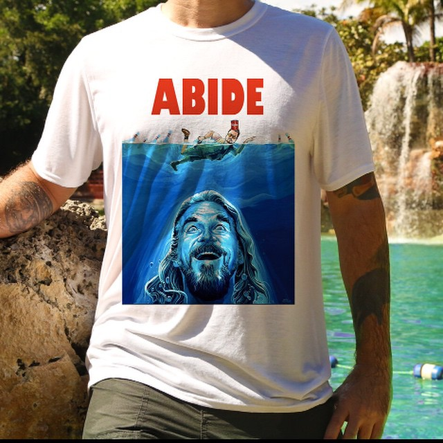 """#Handcrafted #comical #Jaws #poster #parody, #ABIDE #FineArtPrint by renown #artist #DaveMacDowell -#BigLebowski T-#Shirt. Ultra soft sublimated """"#ABIDE"""" Fine Art Print featuring #TheDude attempting to breach on Roger swimming with #Donny's ashes. This unique Tee will keep the heads turning ... Great for watching your favorite #Cohenbrother's flicks, the annual #Lebowskifest, #bowling, #micturating on rugs, and your self-esteem."""
