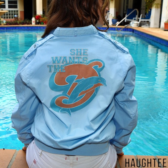 """#Handcrafted #Vintage #MiamiDolphin's Member's Only Style Light Blue #Jacket in great condition. Comical """"#SHEWANTSTHED"""" print on the back. This unique Vintage #Football #Sports Jacket is an incredibly #hilarious vintage piece. This one of a kind Sports Jacket will keep the heads turning ... Great for Miami Dolphin's Games, watching sports at the local #bar, and your self-esteem.  THIS JACKET WOULD MAKE YOU MUCH COOLER , AND SIGNIFICANTLY MORE ATTRACTIVE."""