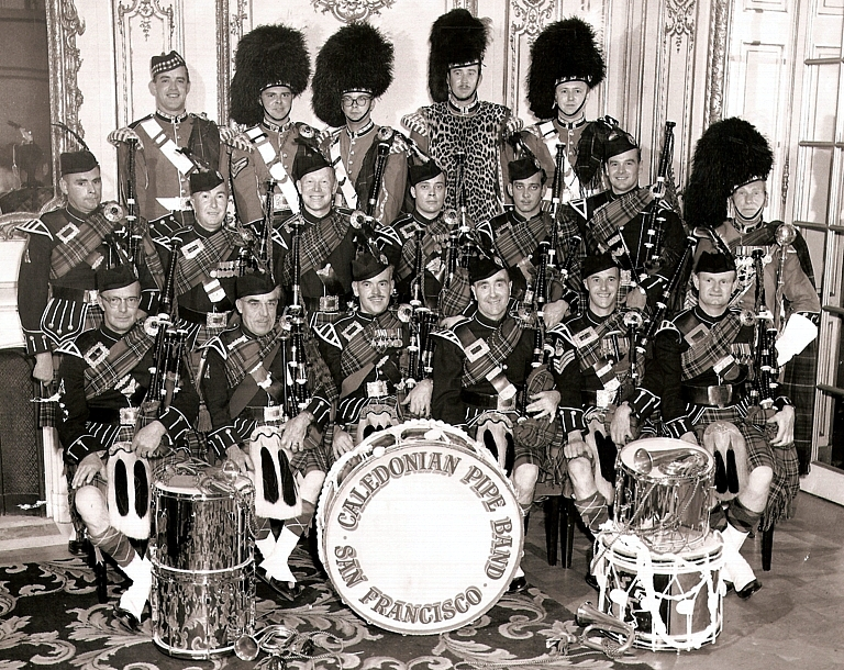 """Photo courtesy of Rick Coffee    Jack Sutherland Jerry Blackstock Rick Coffee Roger Peterson Herb Briggs  John Short Dave Blue Gordon Wardlaw Russ Scholl Gene Wallace John Biggar Geoffrey Baldwin  Don Fiddes Jack MacKenzie Calvin Biggar Tommy Gordon Ian Campbell Ian Begg     Caledonian Pipe Band 1956.   Burn's Night Concert. Note the bugles. The drummers played a """"Retreat"""" as part of the show. The """"Long Reveille"""" and """"Last Post"""" were the bugle tunes along with a certain amount of marching back and forth. It was not a great success. Note, too, that Jack MacKenzie is wearing a sash -- it was blue and given to him for 40 years in the band."""