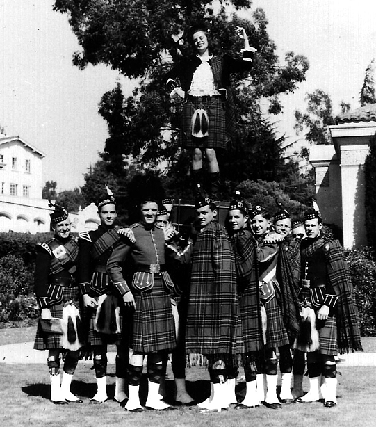 """Photo courtesy of Fred Rutledge   Piedmont High School Kiltie Band ( March 1946).  My Aunt Phyllis MacKay (later Howard) is the Highland Lassie standing on the bass  drum. Glen """"Brick"""" Johnson is the gentleman standing on the left side of the band. He played with the band from the time he started it in 1932 until he retired some 30 years later. [by Fred Rutledge]"""