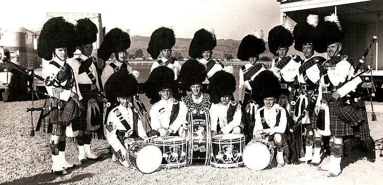 """Photo courtesy of Rick Coffee  Vic Biswell Ozzie Reid Dave Blue Bruce Flood Charlie Dawson John Partnon Jim King Don Fiddes Calvin Biggar  Willie McEarlan Jack Sutherland George McKay Rick Coffee Bert Thompson     Caledonian Pipe Band 1959 - 1960 (?).   Petaluma/Santa Rosa Games. (Names to the best of my recollection - spelling questionable). My recollection is that Ozzie Reid and Willie McEarlan were still with the 6th Army Pipe Band at the time and that Vic Biswell (who had been Pipe Major there) asked them to help out. Bert Thompson took over as Drum Sergeant later. The white jackets were a new addition for summer taking the place of the """"Piper Green"""" and Red with """"Crown Lace"""" tunics seen the other photos of the band. Pipers wore """"Royal"""" and Drummers """"Hunting"""" Stewart tartan. [by Rick Coffee]"""