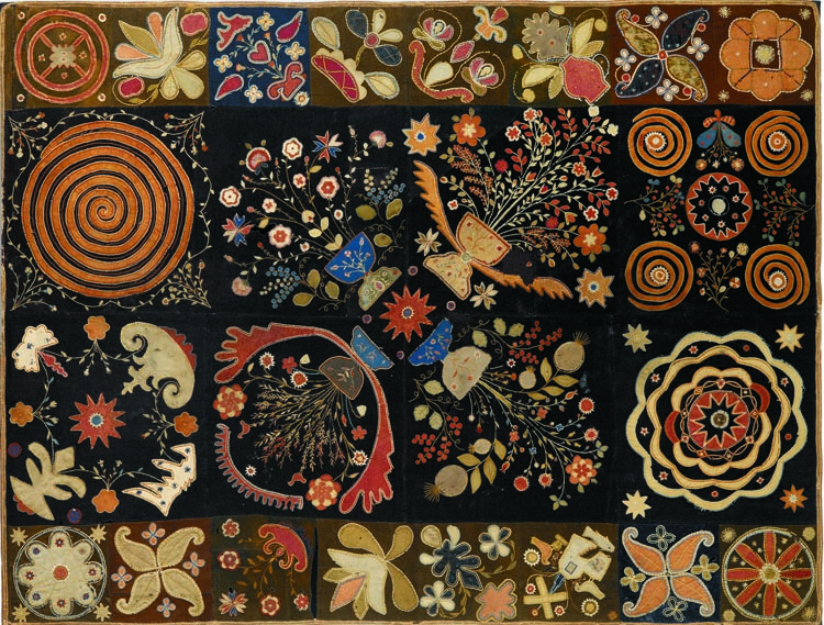 """It's one of my favorite pieces. I love the imaginative, freeform design and the color scheme,"" Grace Snyder says of the circa 1810–20 pieced and embroidered wool-on-wool with silk applique New England table rug, which hangs over the bed in the master bedroom."
