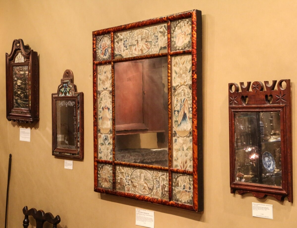 Mirrors, mirrors, on the wall. A selection of looking glasses included, from right, a New York or New Jersey carved and pierced maple example with hearts, pinwheels and half-circles; a Seventeenth Century English needlework mirror from the collection of Irwin Untermyer that had been exhibited at the Metropolitan Museum of Art in 1945; and a North European Eighteenth Century courting mirror with etched mirror plate. Elliott and Grace Snyder, South Egremont, Mass.