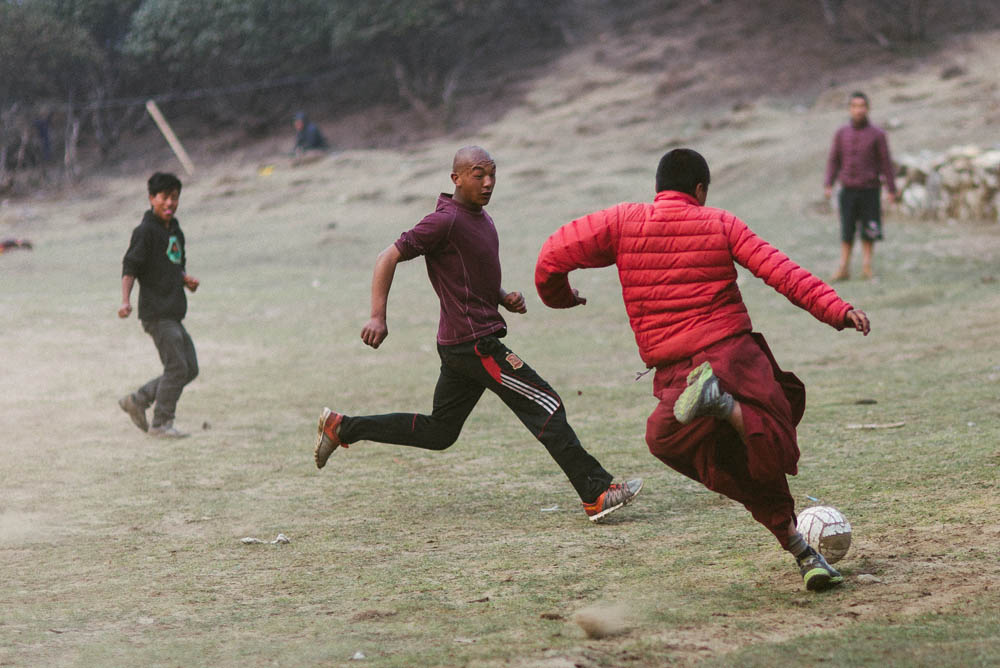 Tibetan monks enjoying a round of soccer with local porters and tourists.