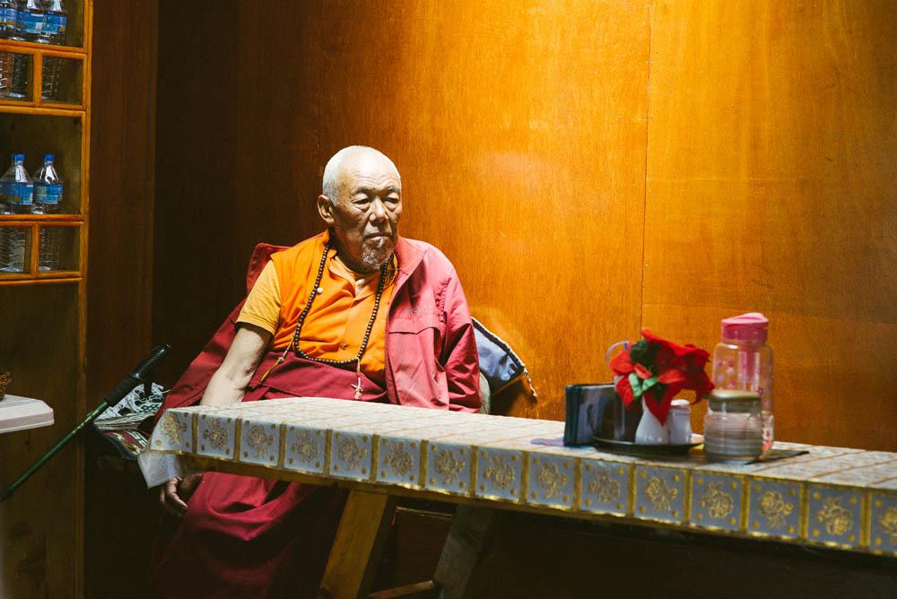 Tibeten monk resting under the light by the dinner tables.
