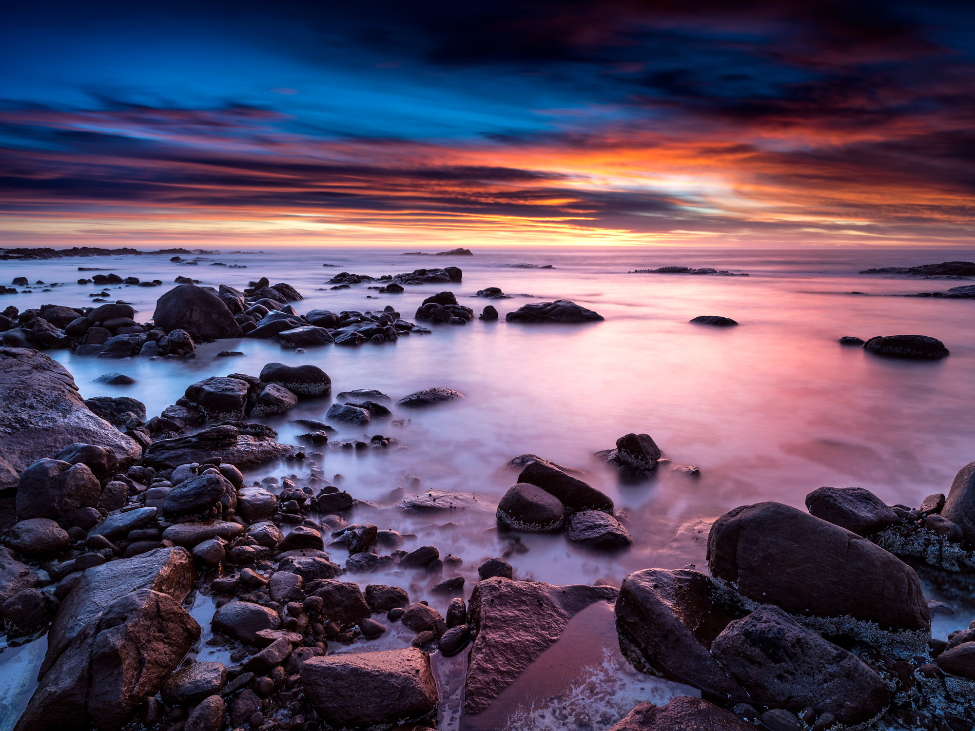 Long exposure seascape in Dunsborough with brightly colours sunset sky.