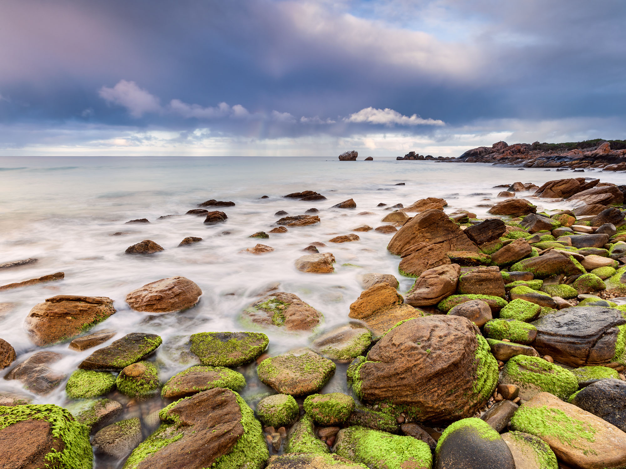 Mossy foreshore and rocks with stormy skies.