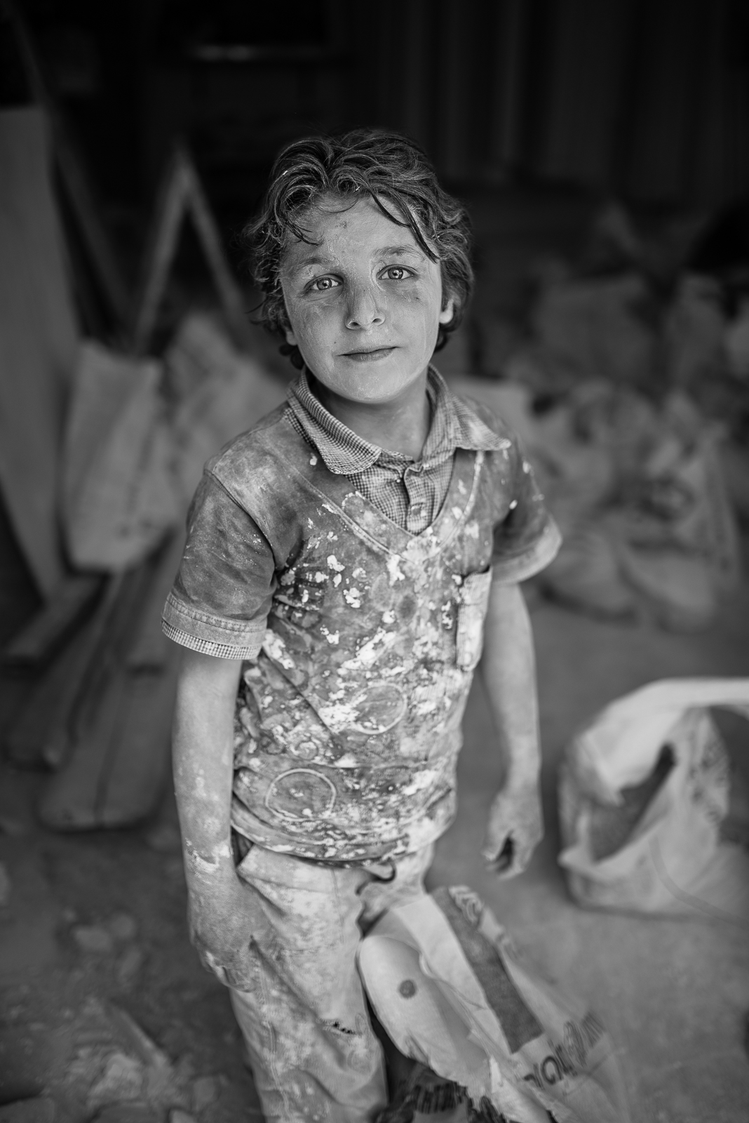 Kilis. The work of a little syrian boy:carry cement bags inside a house under construction