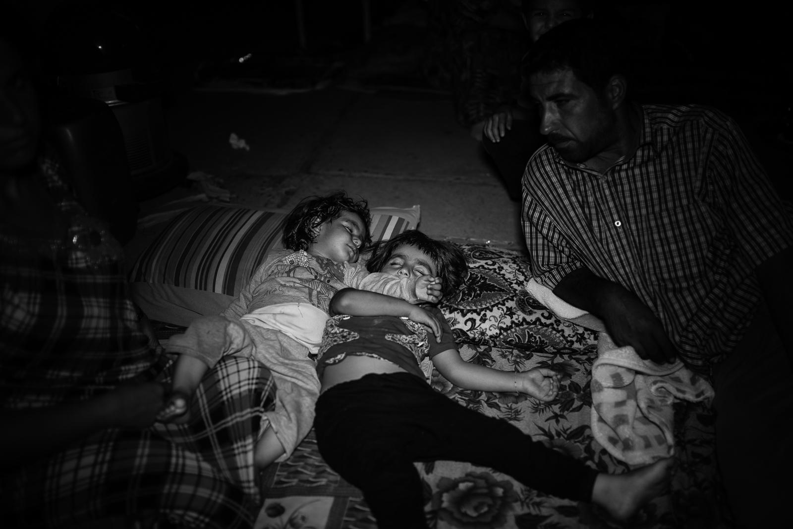 Children sleeping on the floor of a school's garden in Zakho