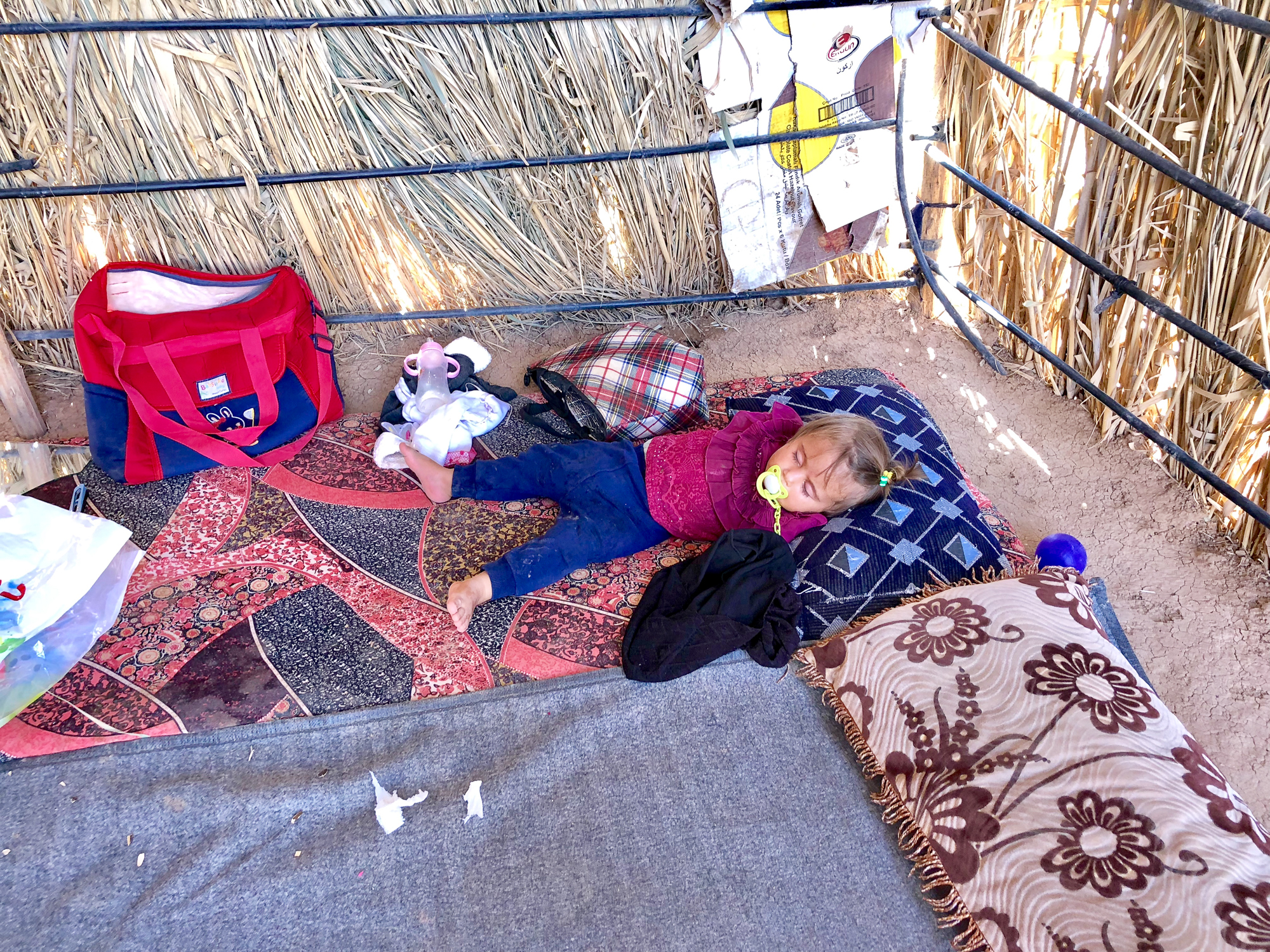A young yazidi girl is sleeping in a house made of straw