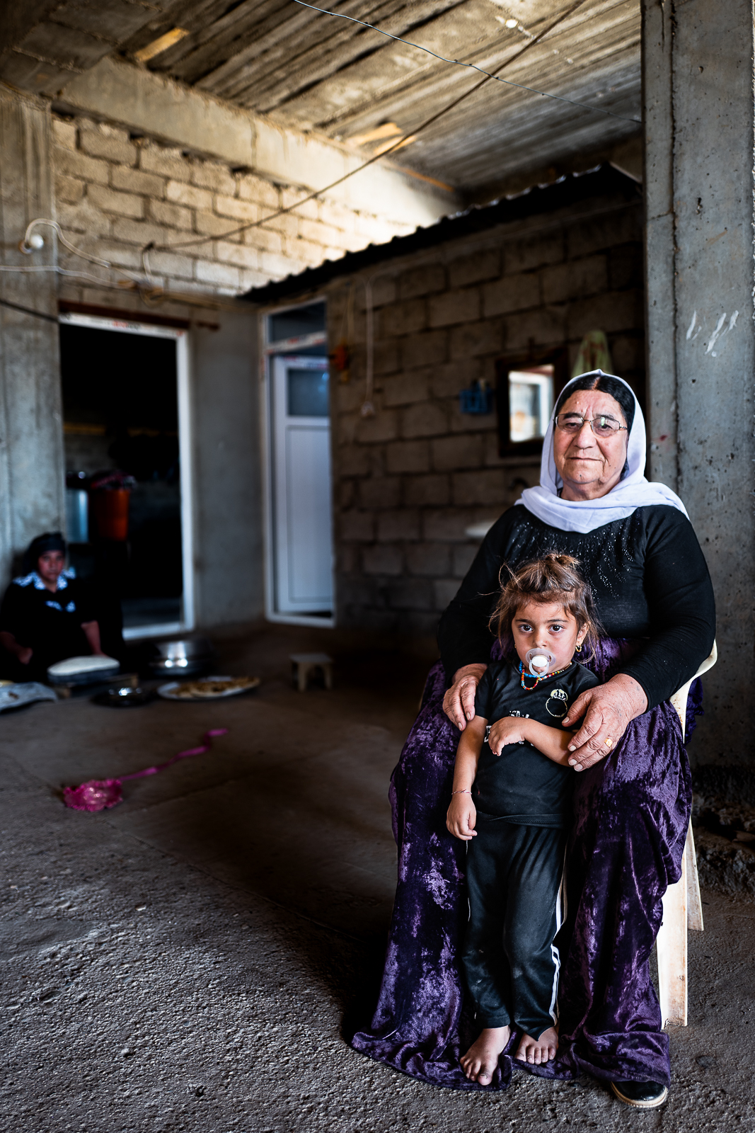 A little girl and his grandmother in an unofficial camp in Sharya, near Dohuk