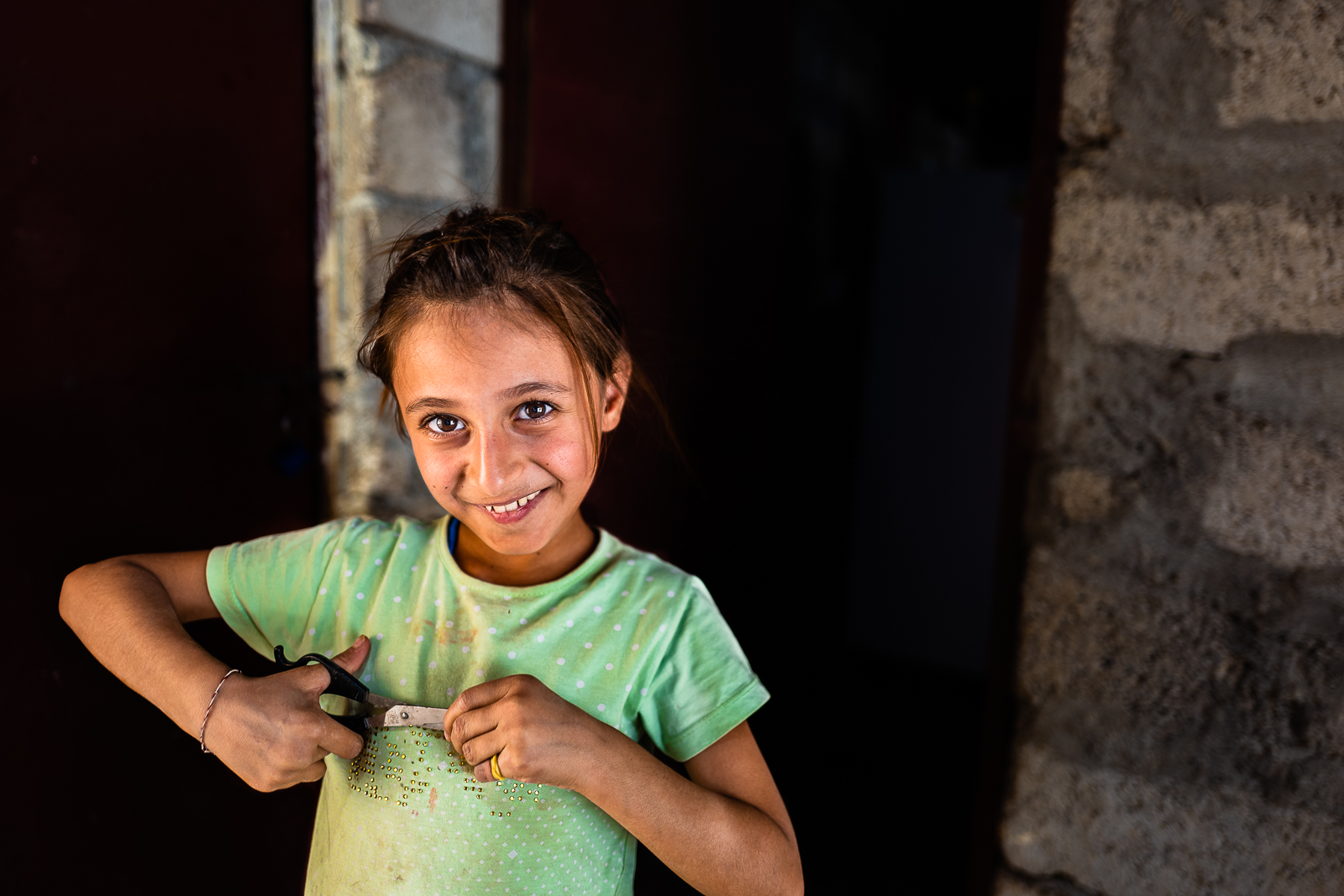 A little girl is cutting her nails in a unofficial camp in Sharya, near Dohuk