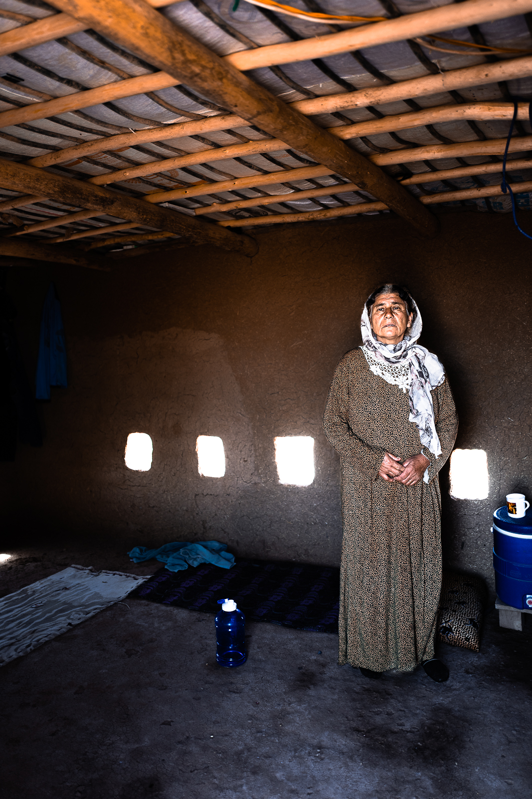 A mother inside her mud house in a unofficial camp in Sharya, near Dohuk