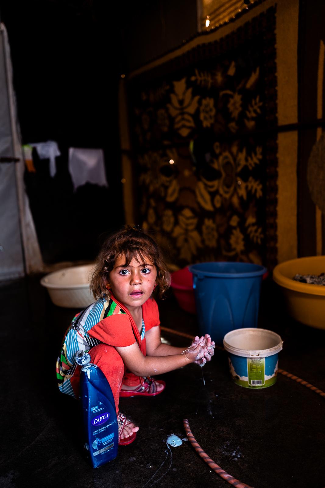 A little girl inside a tent in the refugees camp of Khanik, near Douhk