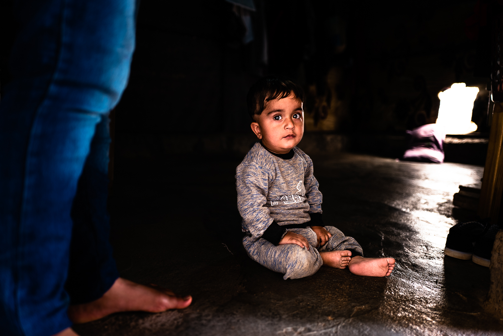 Child on the ground near his mother feet, in a unofficial camp in Sharya, near Dohuk
