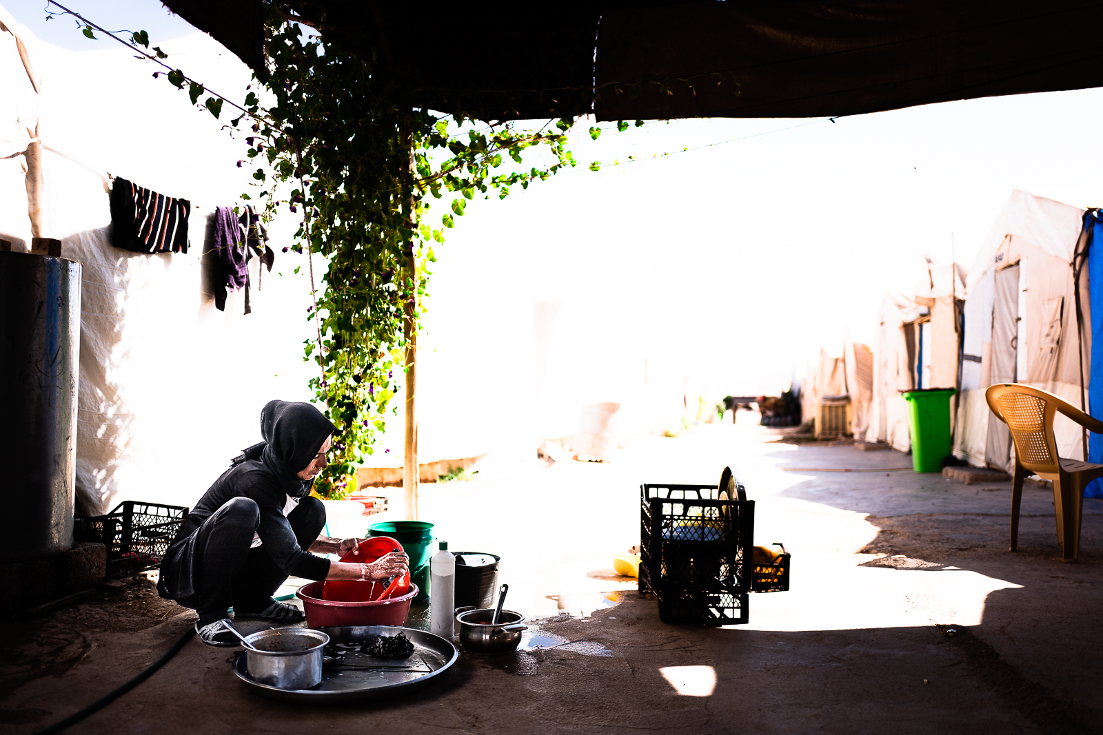 A mother wash the dishes in the refugees camp of Khanik, near Douhk