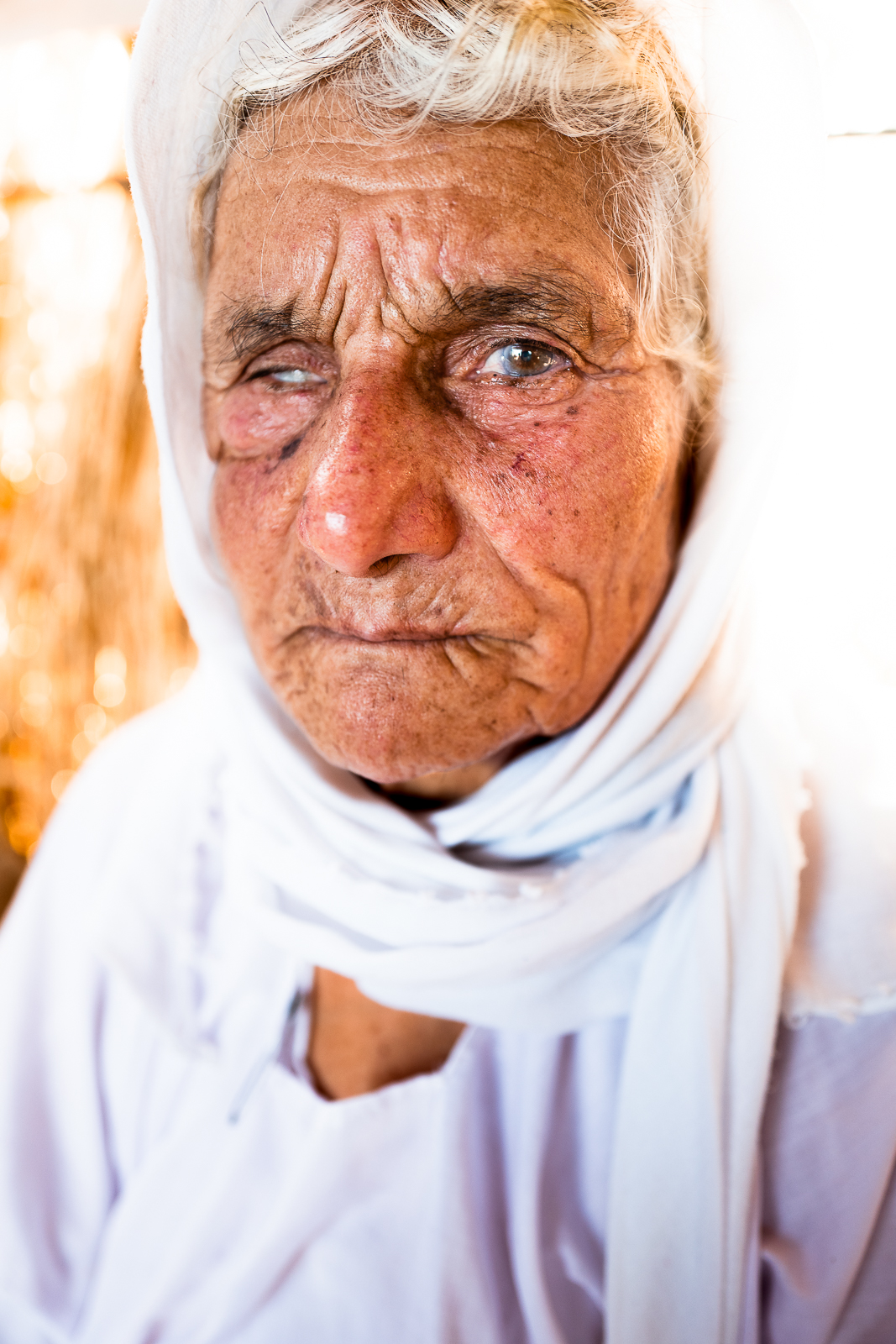 Old woman in a unofficial refugees camp on the border of the street near Douhk