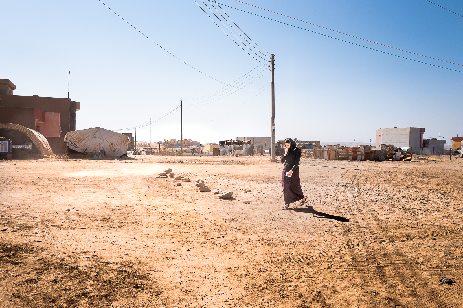 A mother is walking through a sand storm in a unofficial camp in Sharya, near Dohuk