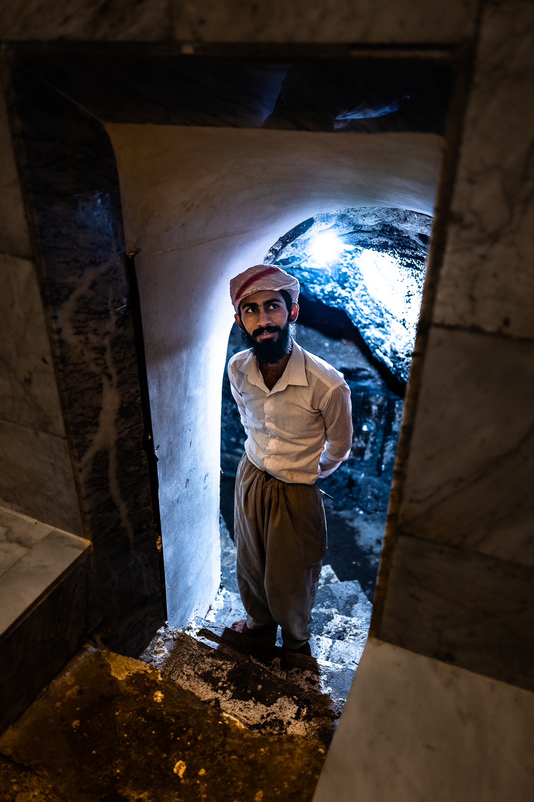 A man from the security is surveilling the holy source inside the stones of Lalish