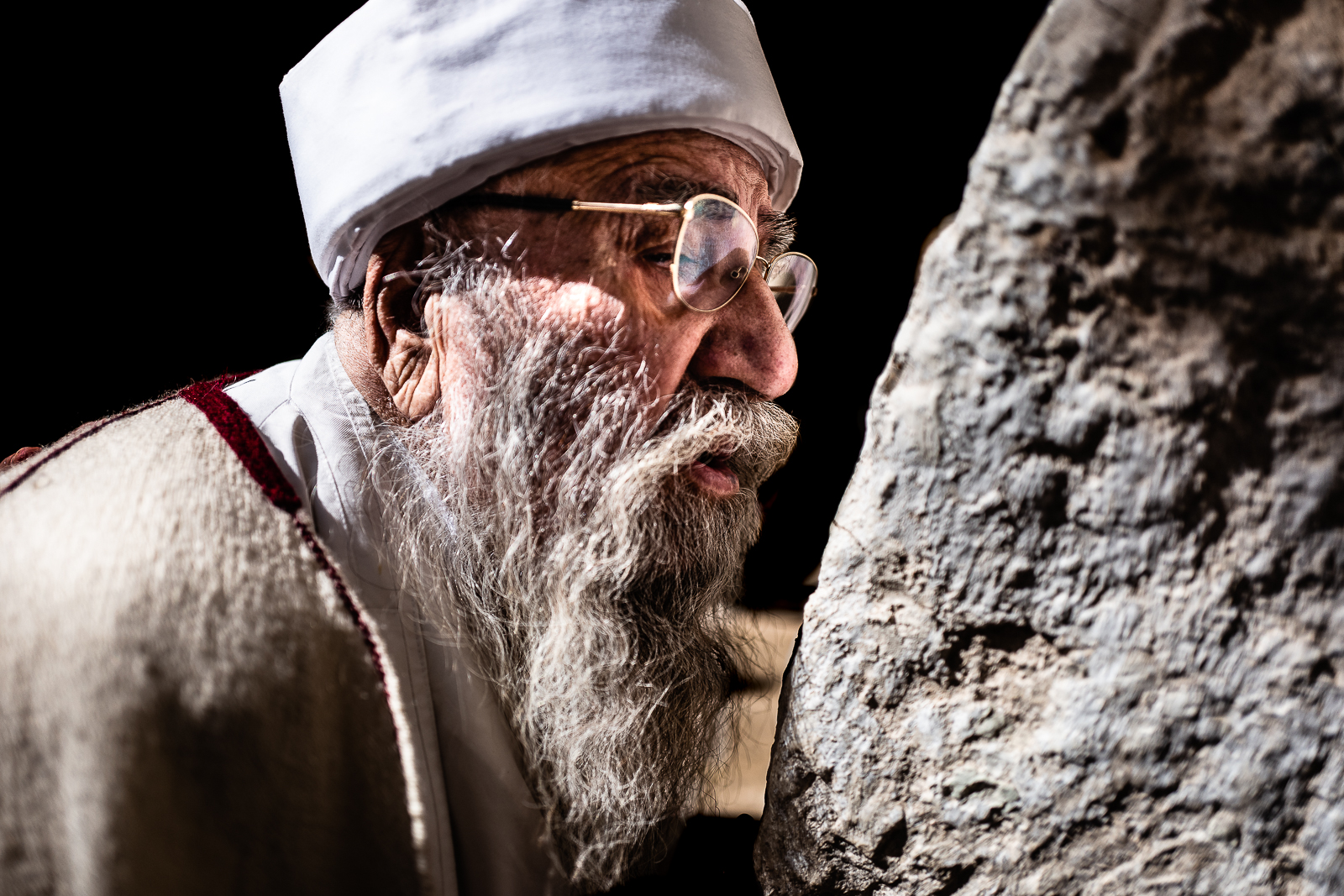 Baba Sheikh is kissing a holy stone in Lalish