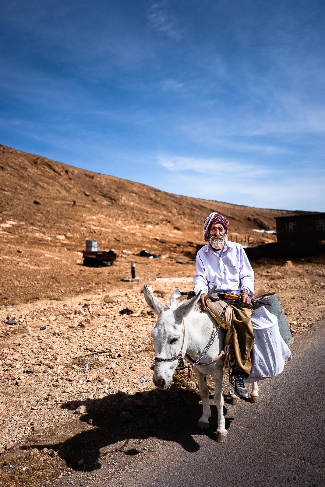 An old man with a Kalashnikov on his donkey. Sinjar mount