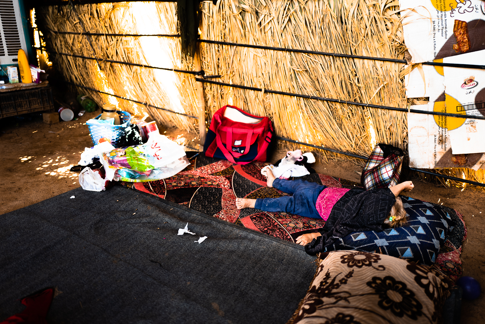 A little yazidi girl sleeping on the ground in a house made of straw, in a unofficial refugees camp on the border of the street near Douhk