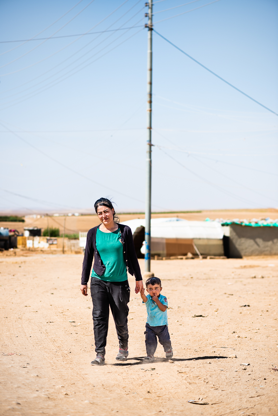 A mother and her son are crossing the street in the unofficial camp in Sharya, near Dohuk