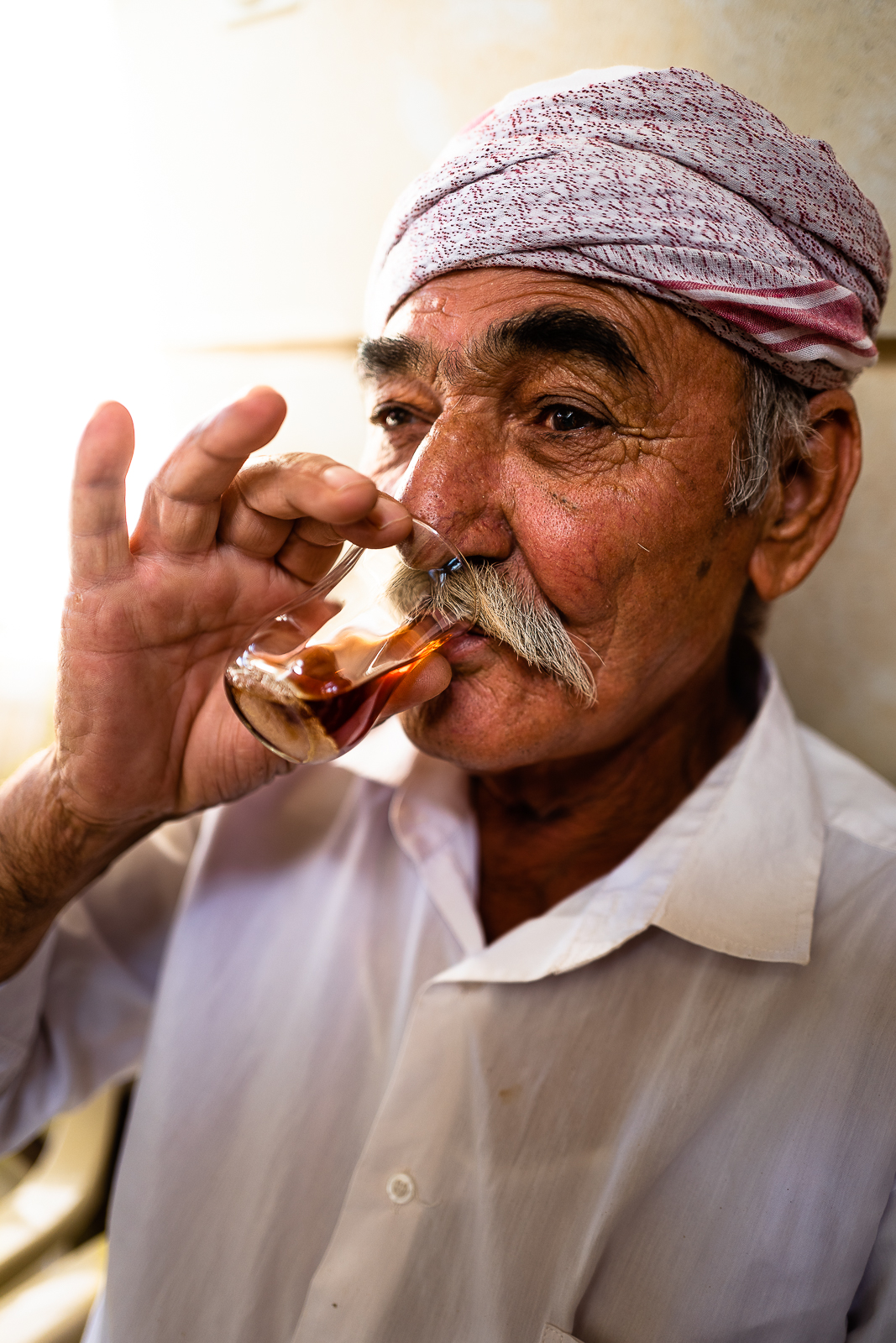 Man is drinking his chai (tea) before the start of Cejna Cemaiya in  Baba Sheikh's house