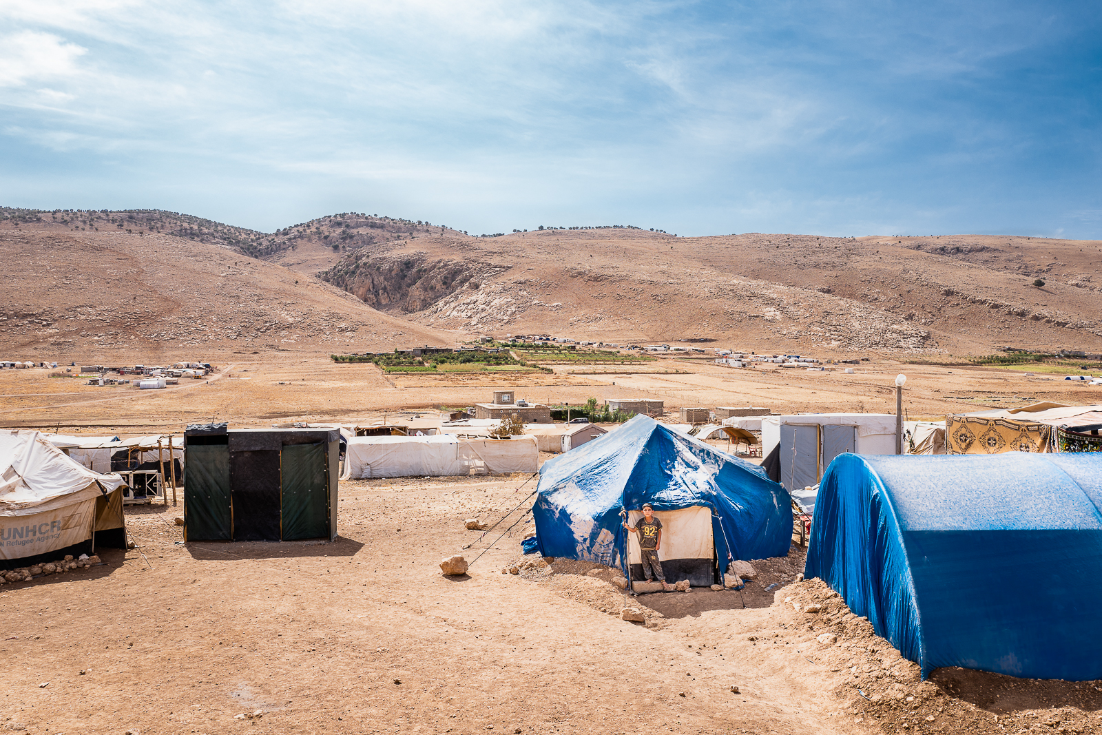 A child is standing outside his tent in Mount Sinjar