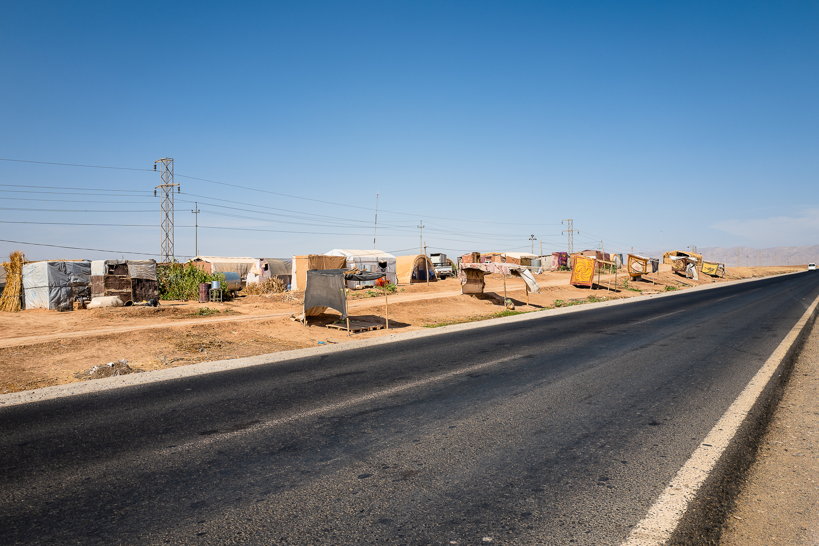 Unofficial refugees camp on the border of the street near Douhk. The yazidi refugees inside this camp are making some money ny selling seeds and vegetables in the tents you can see on the border of the streets