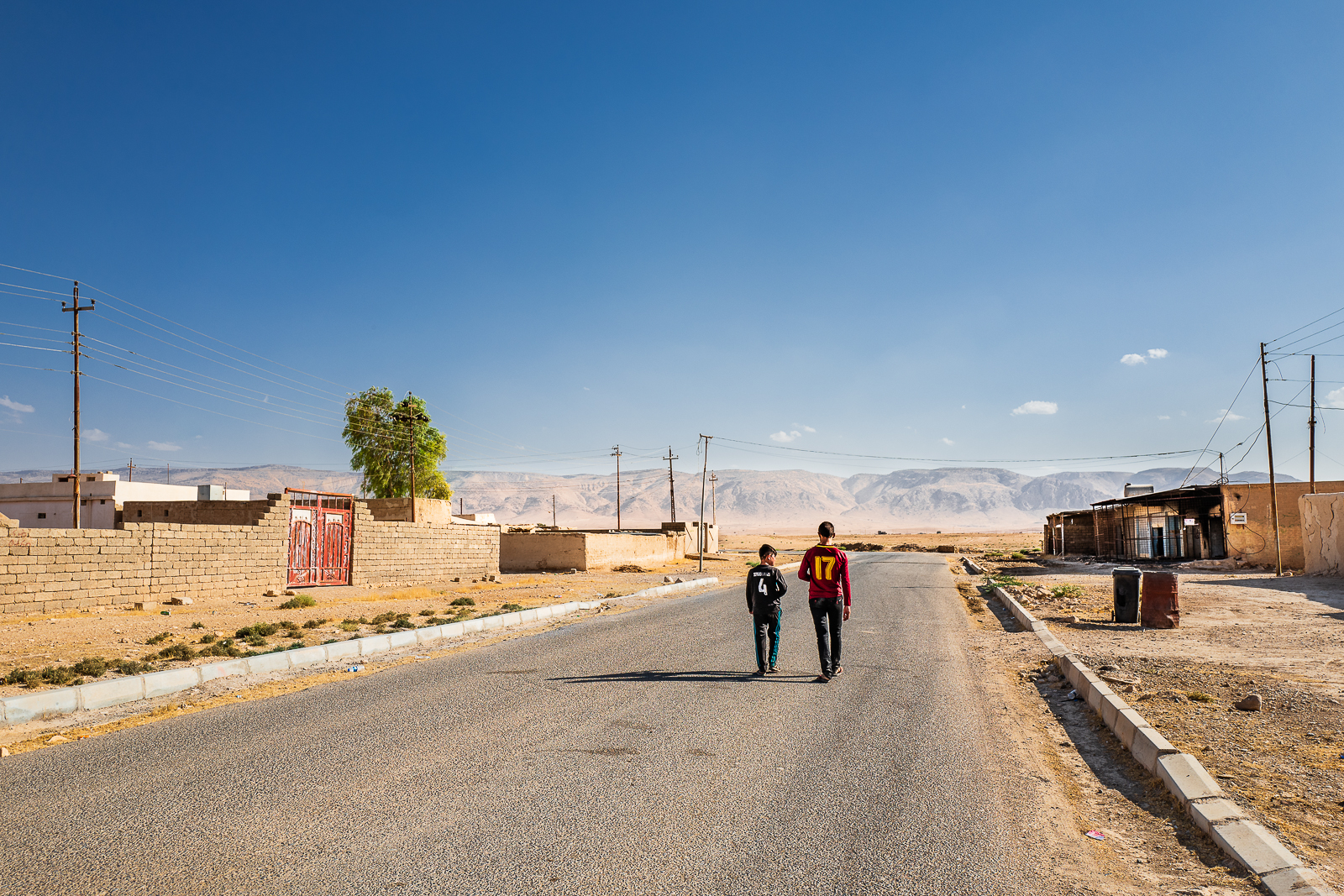 Two boys in an almost empty village under the Sinjar Mount