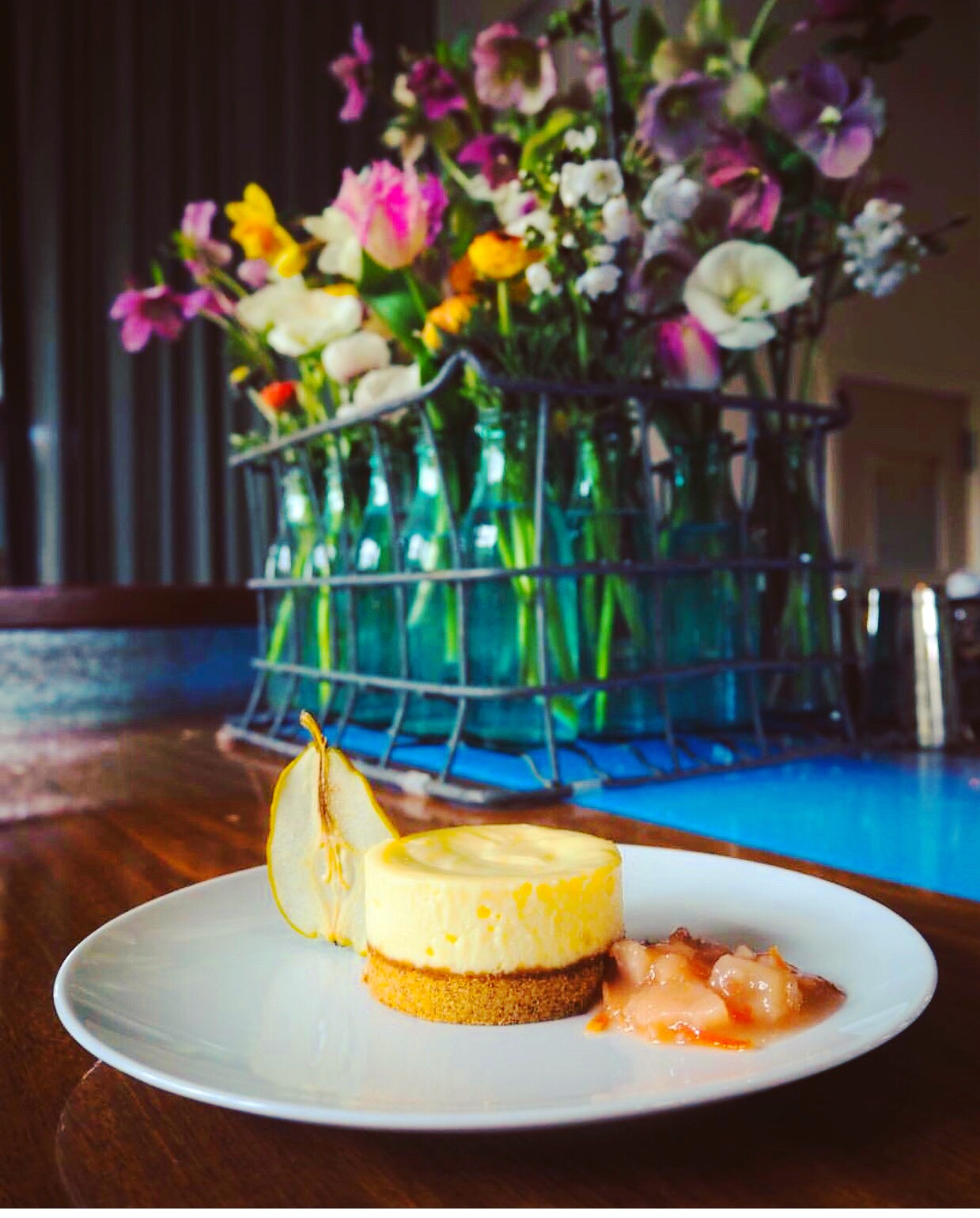 In the Barn: Bellwether Farm's Cheesecake with Barndiva Farm pears, preserved and dehydrated. Spring floral arrangement by Daniel Carlson. Image by Eva Perla, a German journalist writing about the history of farm to table in Healdsburg.