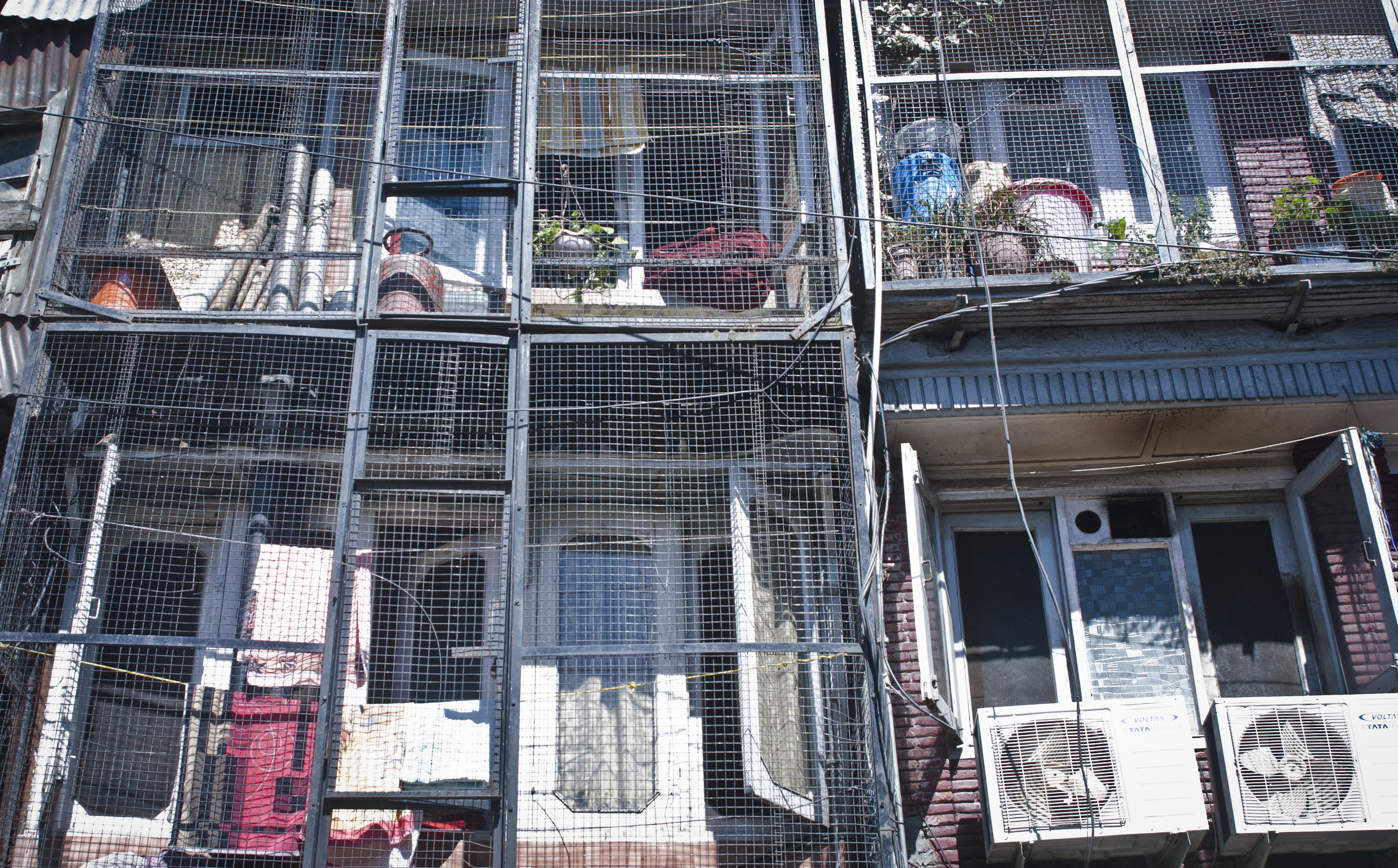 Cages are put around porches to protect homes and belongings from monkey intruders