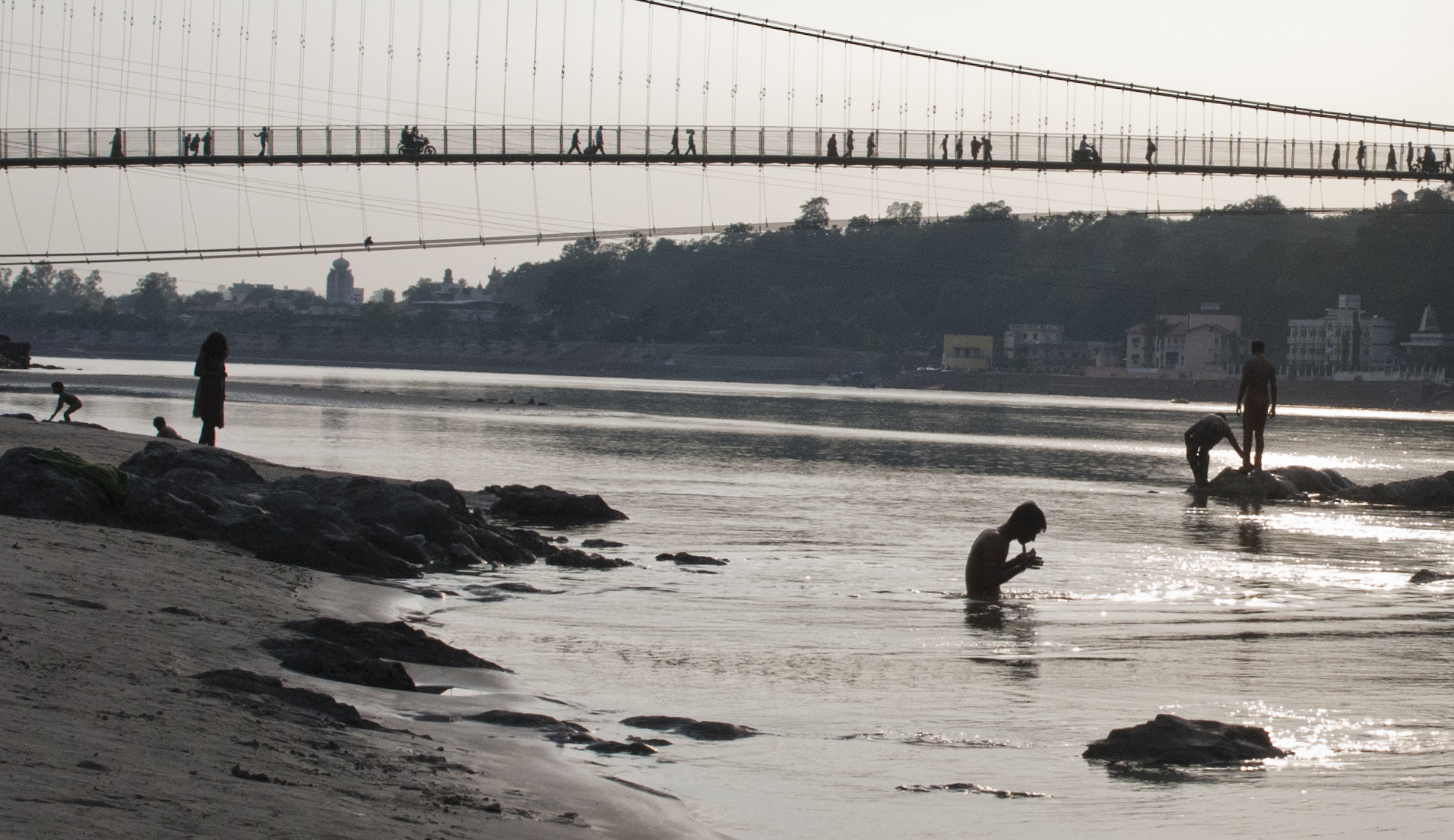 Underneath Ram Jhula bridge pilgrims and locals bathe in the holy water of the Ganges.