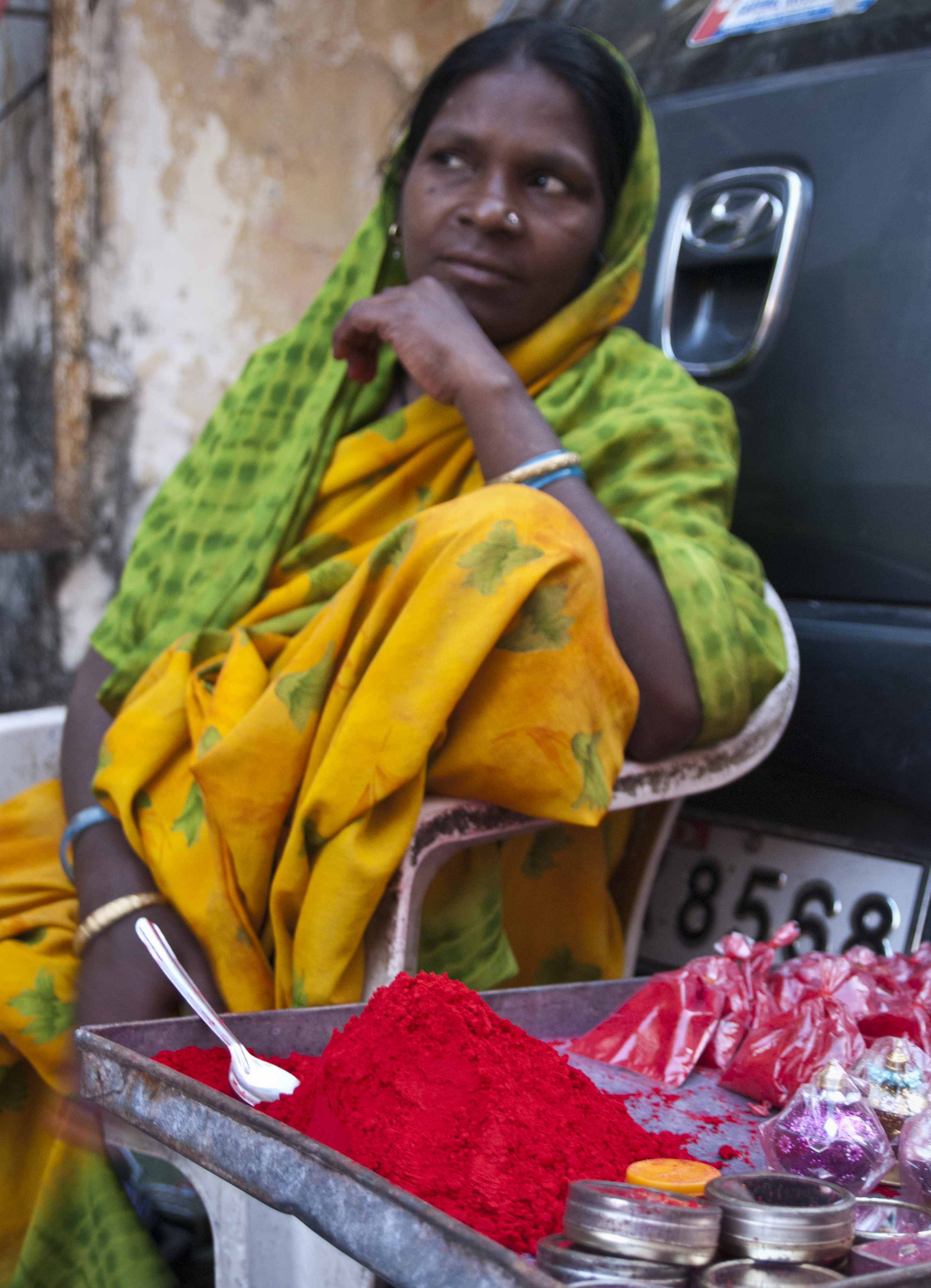 A woman sells vermillion powder. The powder is applied between the eyebrows to signify the third eye and the sixth chakra.