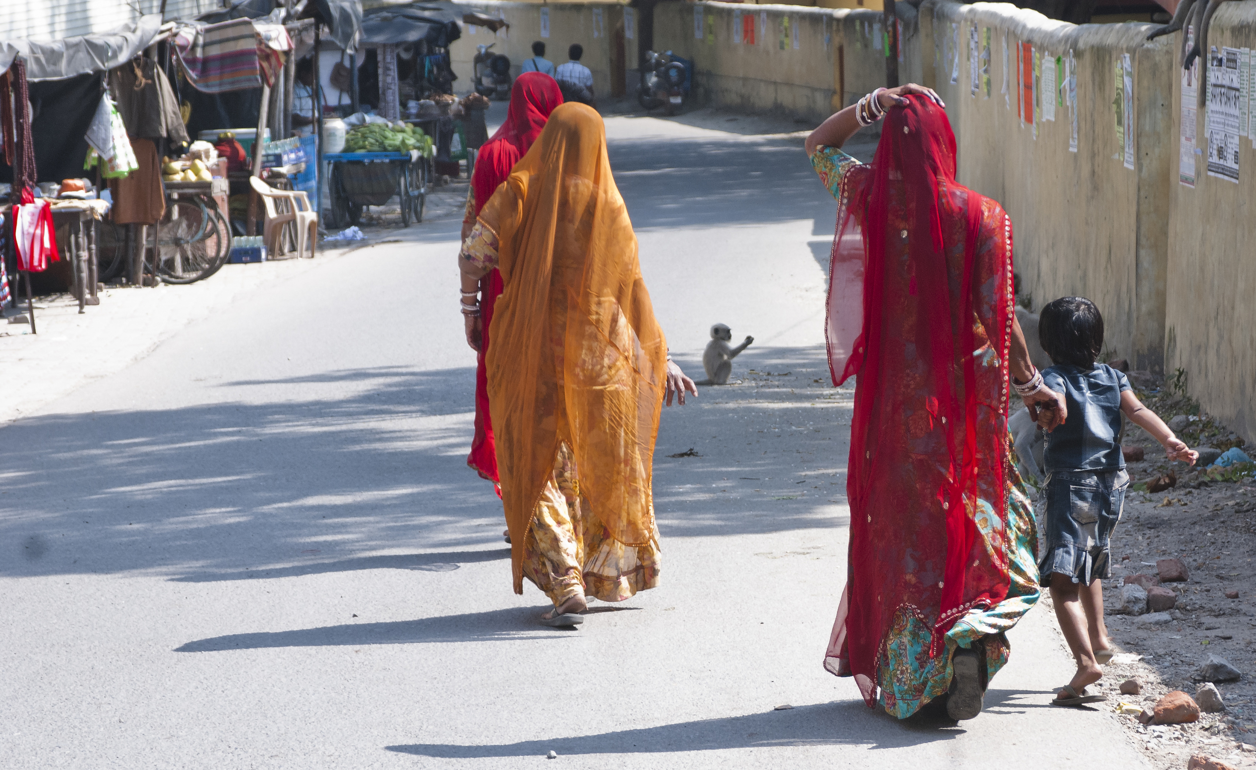 Woman walk down a road towards Lakshman Jula in the direction of Rishikesh.